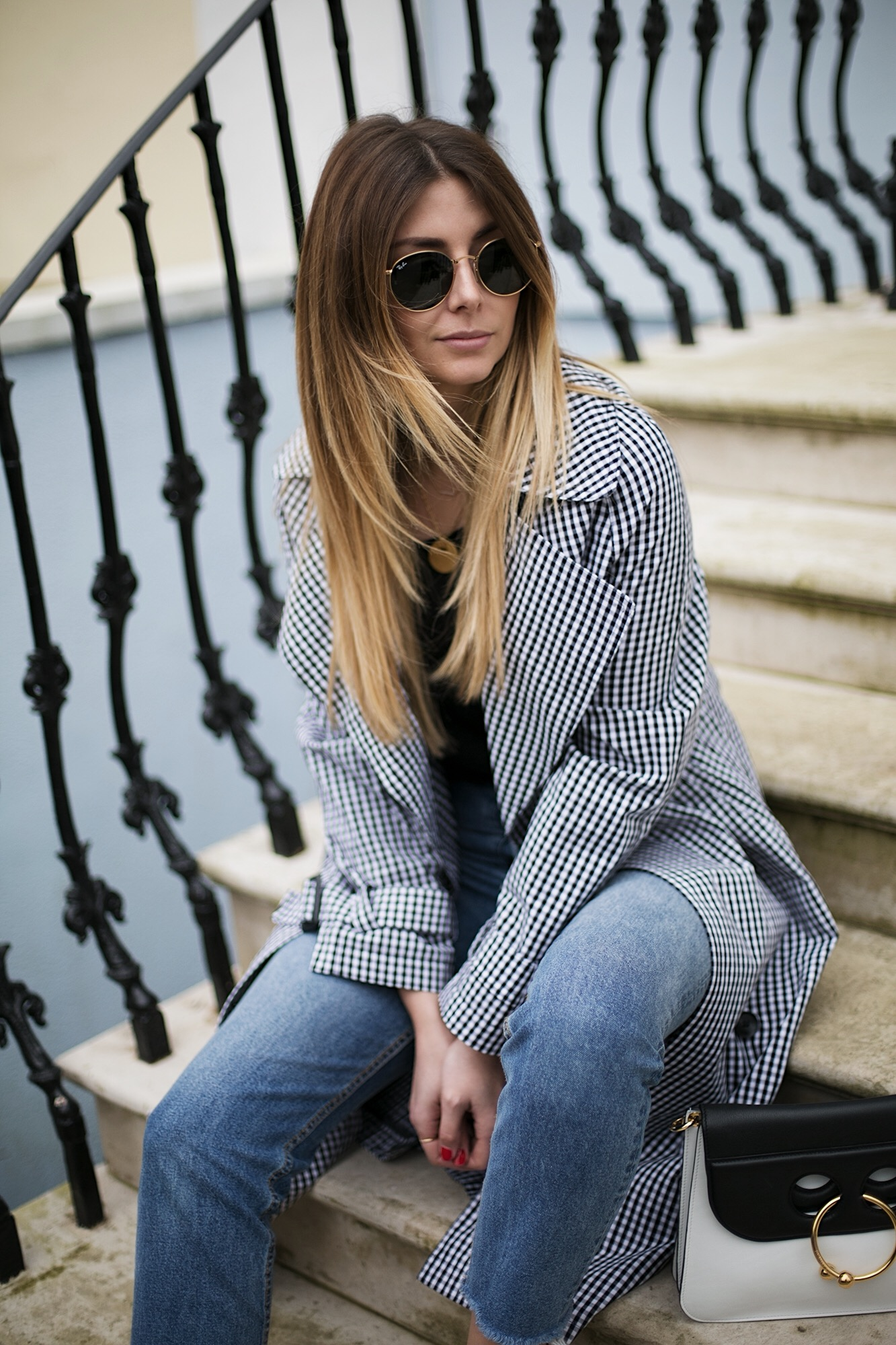 Gingham trench coat, black t-shirt, frayed hem jeans, J.W. Anderson Pierce bag, Rayban round sunglasses