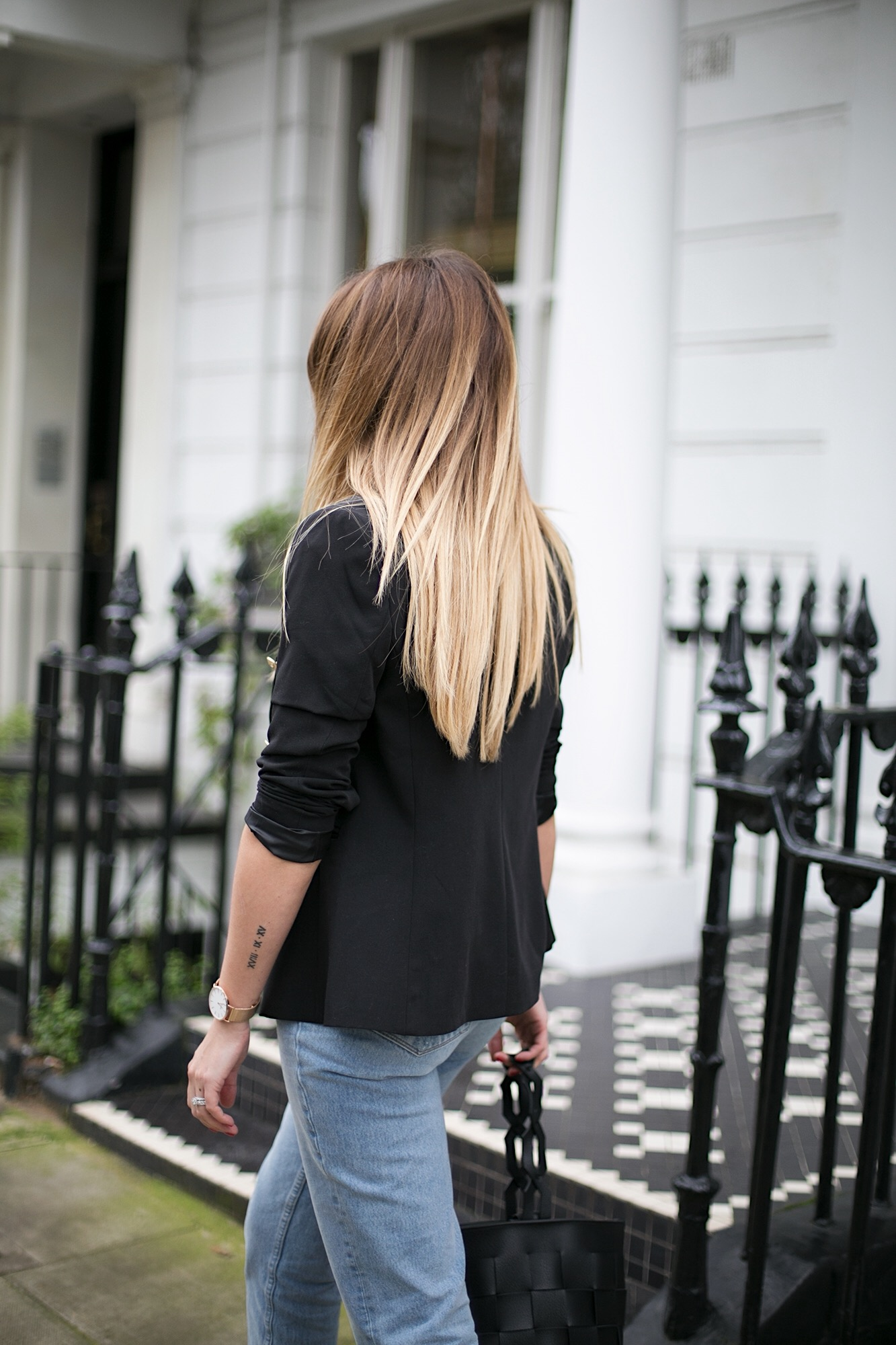 long blonde balayage hair, black blazer, rose gold watch, tiny Roman numerals arm tattoo, bleach wash jeans
