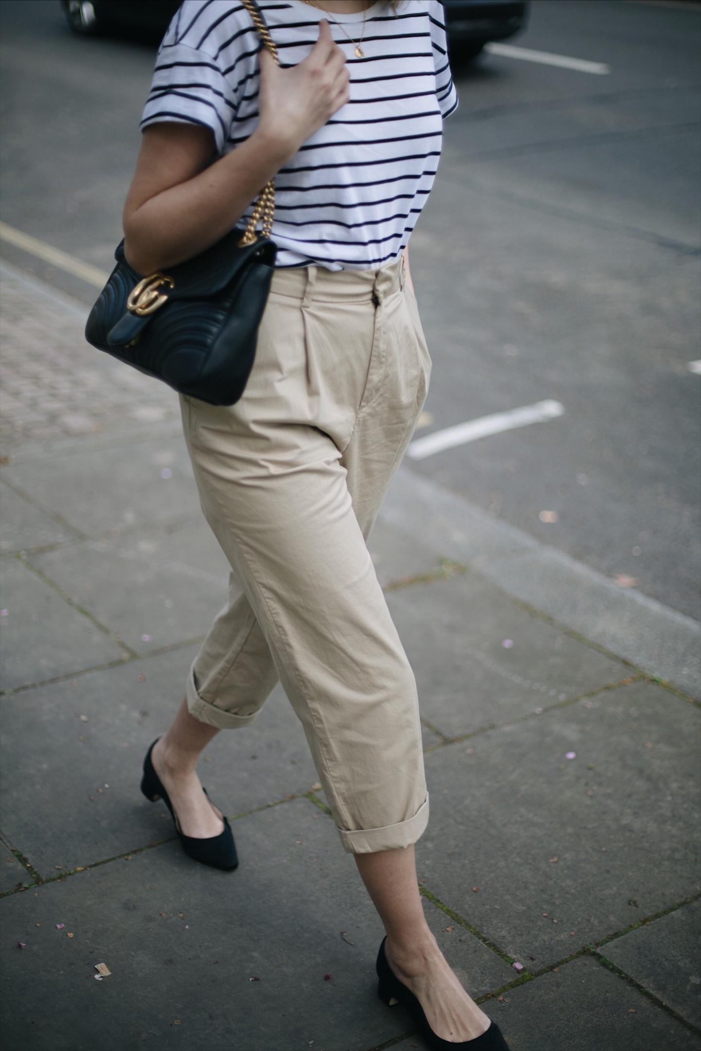 Emma Hill wears Dune x Rupert Sanderson 'Grace Hi' black satin low heels, beige high waisted chino trousers, stripe t-shirt, Gucci Marmont bag