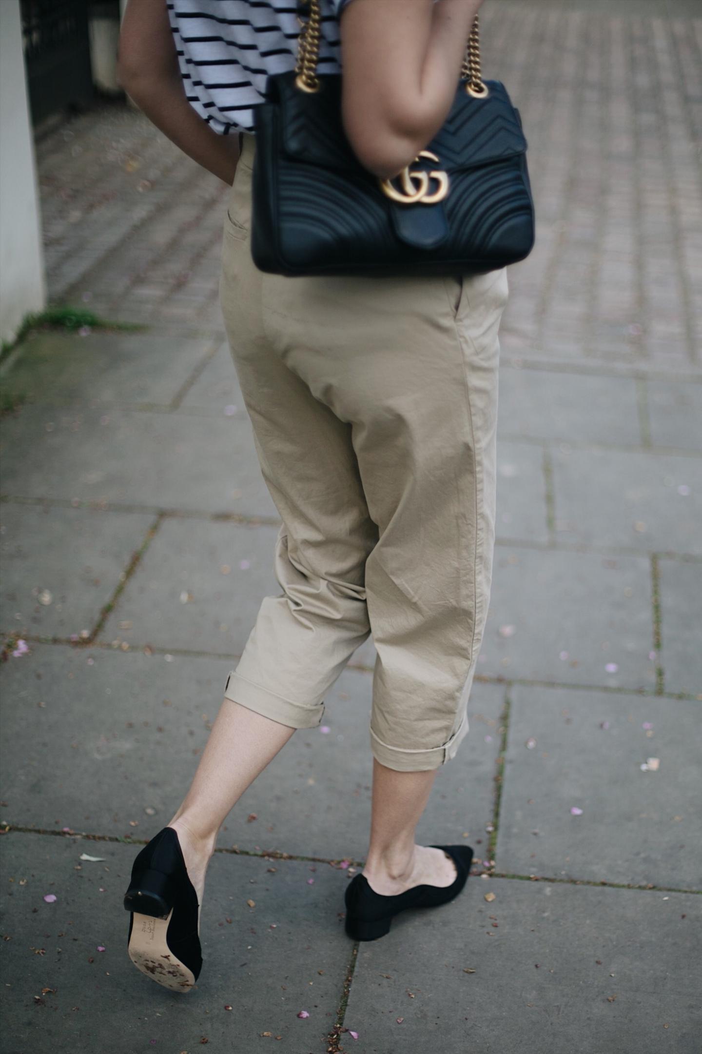 Emma Hill wears Dune x Rupert Sanderson 'Grace Hi' black satin low heels, beige high waisted chino trousers, stripe t-shirt, Gucci Marmont bag