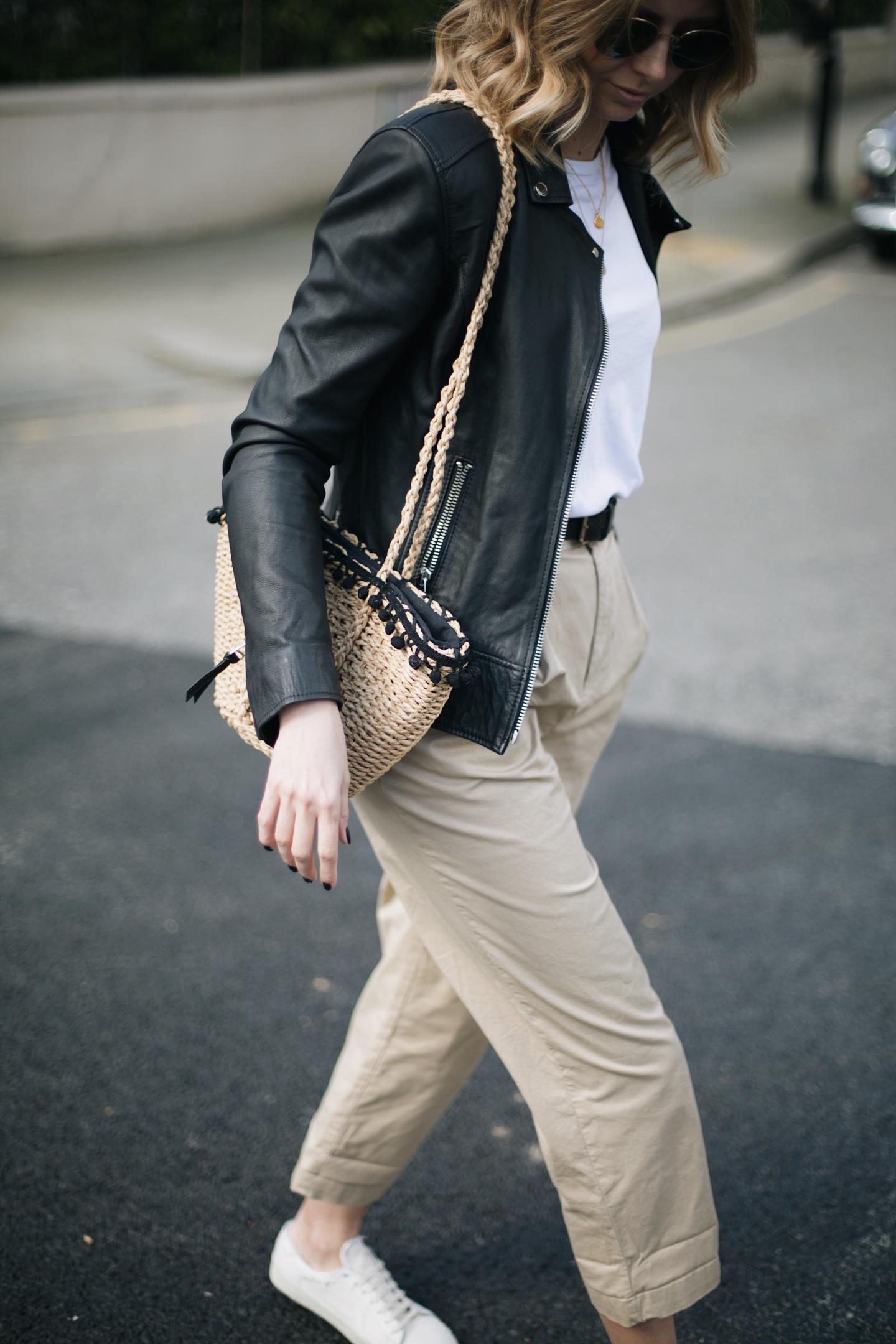 Emma Hill wears black leather biker jacket, basic white t-shirt, beige high waisted chinos, straw basket bag, Saint Laurent trainers