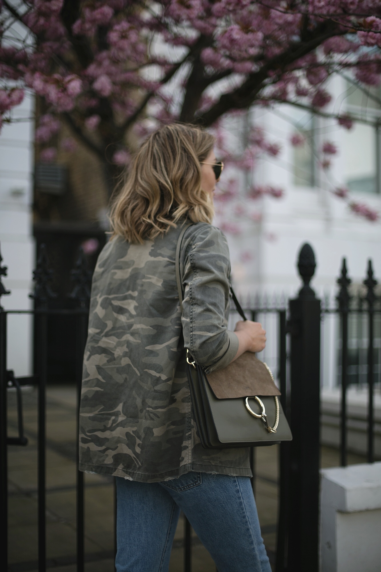 Emma Hill wears camo jacket, khaki Chloe Faye bag, mid wash jeans, casual Spring outfit