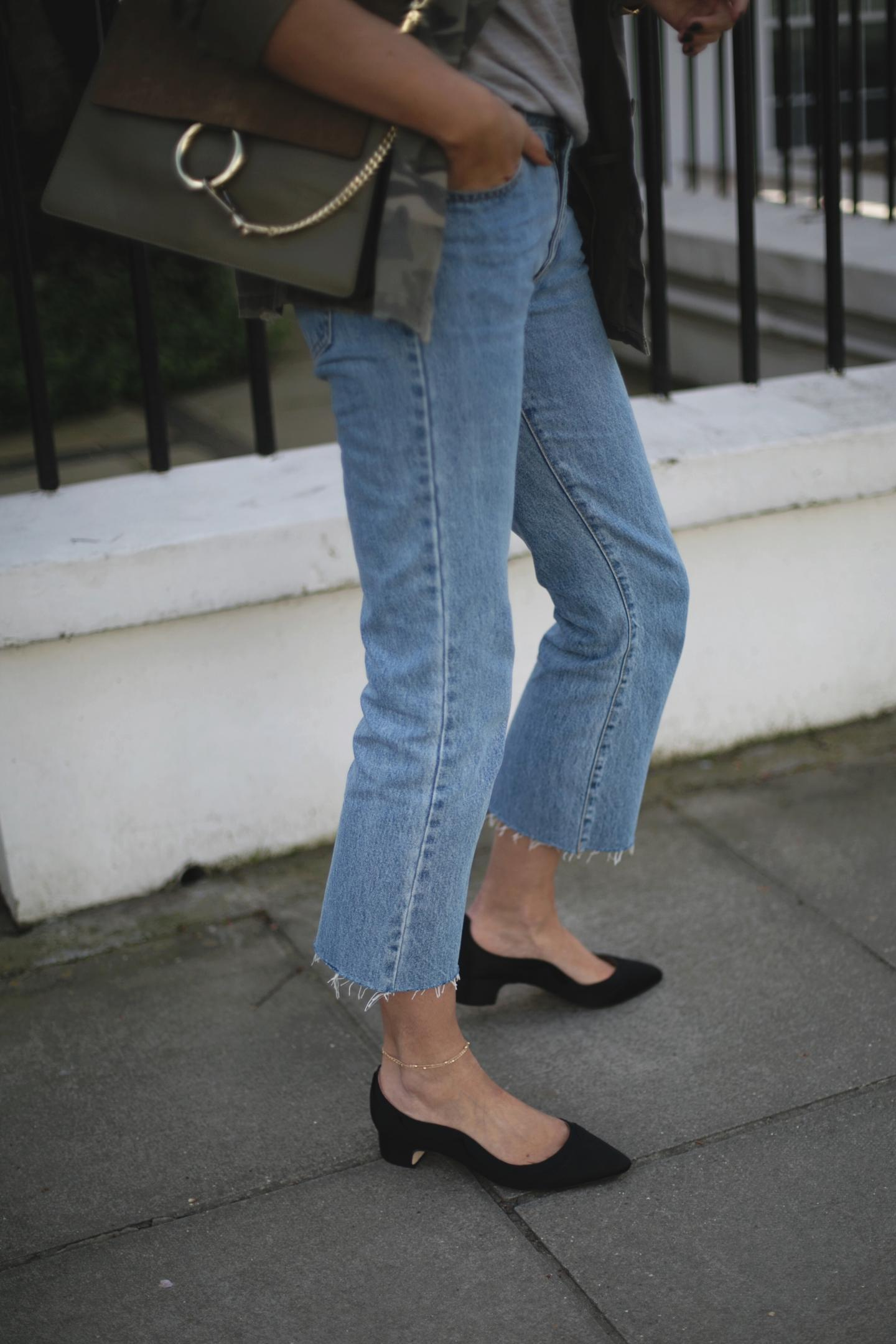 Emma Hill wears khaki Chloe Faye bag, cropped mid wash frayed hem jeans, dune x Super Sanderson black satin low block heels, camo jacket, grey t-shirt