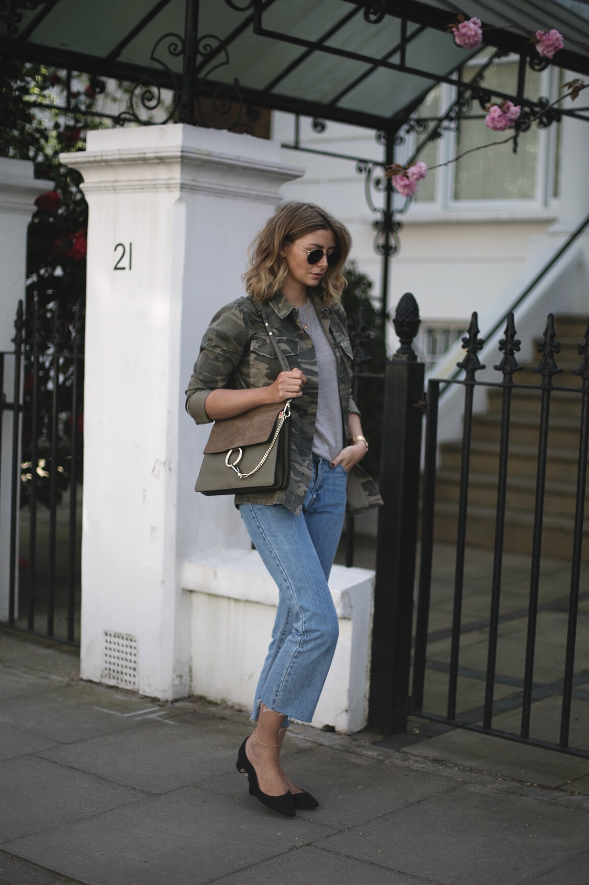 Emma Hill wears camouflage jacket, grey linen t-shirt, khaki Chloe Faye bag, cropped frayed hem light wash jeans, Dune x Rupert Sanderson low block heels, round Rayban sunglasses, gold jewellery, casual Spring outfit