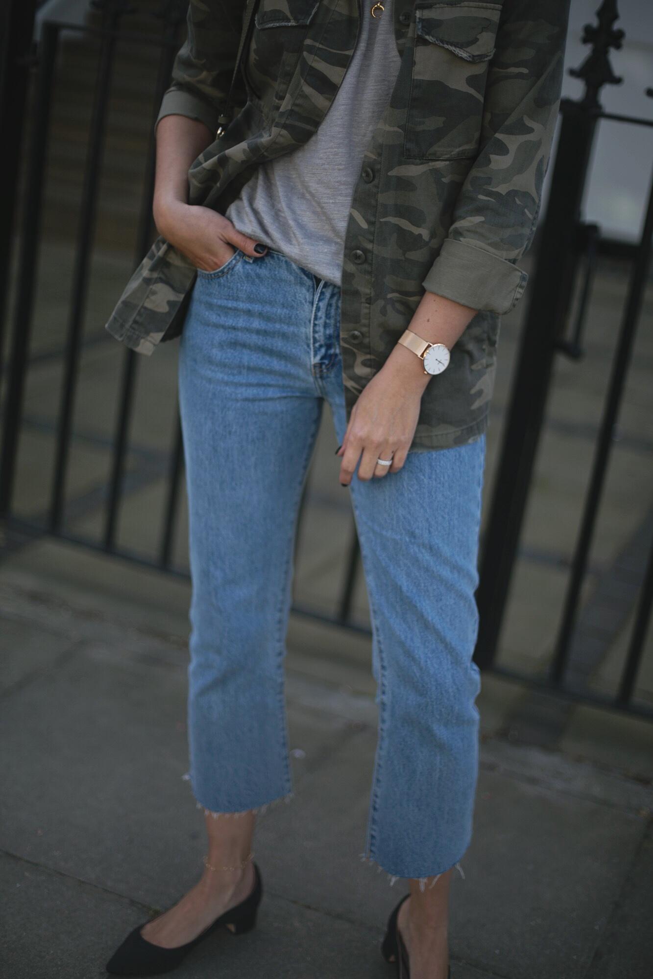 Emma Hill wears khaki Chloe Faye bag, cropped mid wash frayed hem jeans, dune x Super Sanderson black satin low block heels, camo jacket, grey t-shirt, rose gold watch