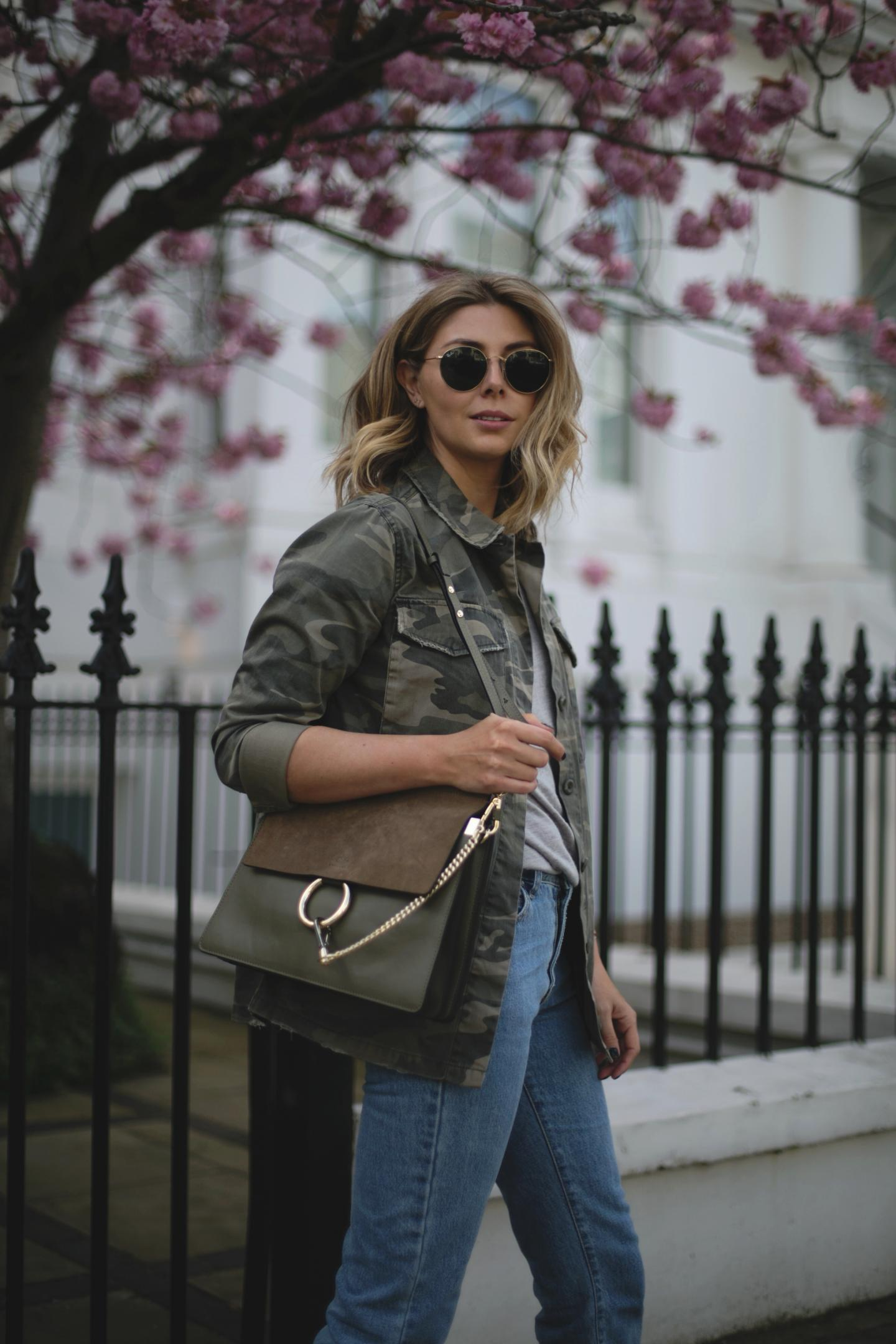 Emma Hill wears camo jacket, khaki Chloe Faye bag, mid wash jeans, round Rayban sunglasses, casual Spring outfit