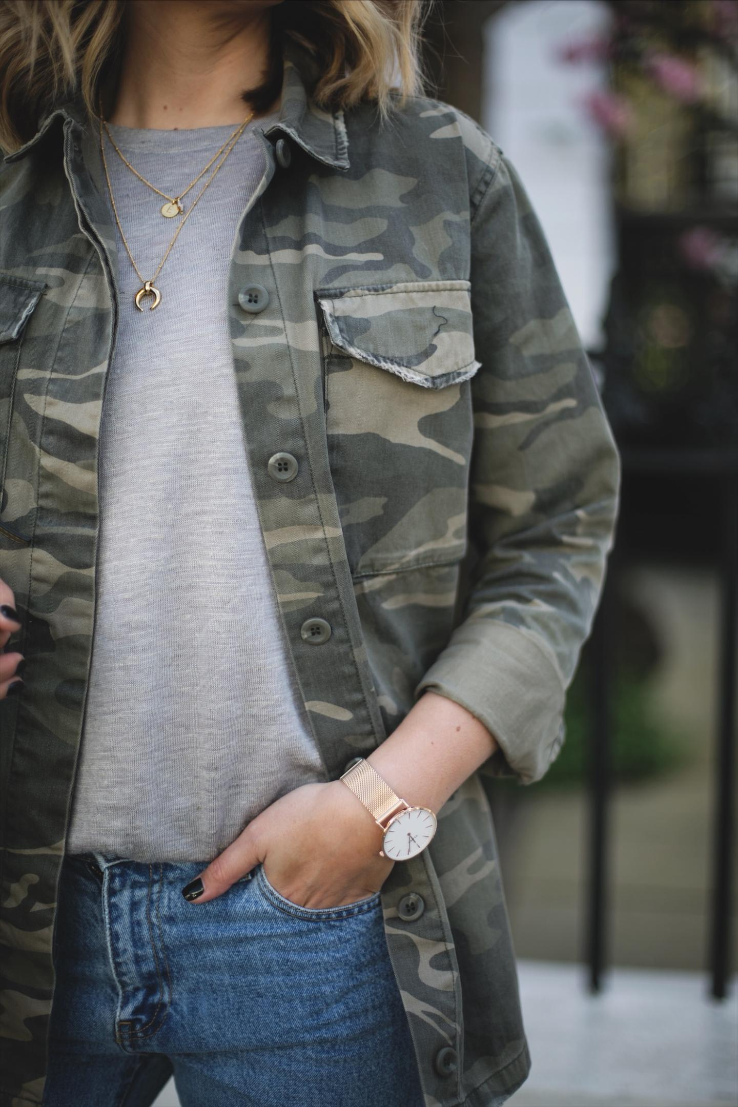 Emma Hill wears camouflage jacket, grey linen t-shirt, light wash jeans, rose gold watch, gold jewellery, casual Spring outfit