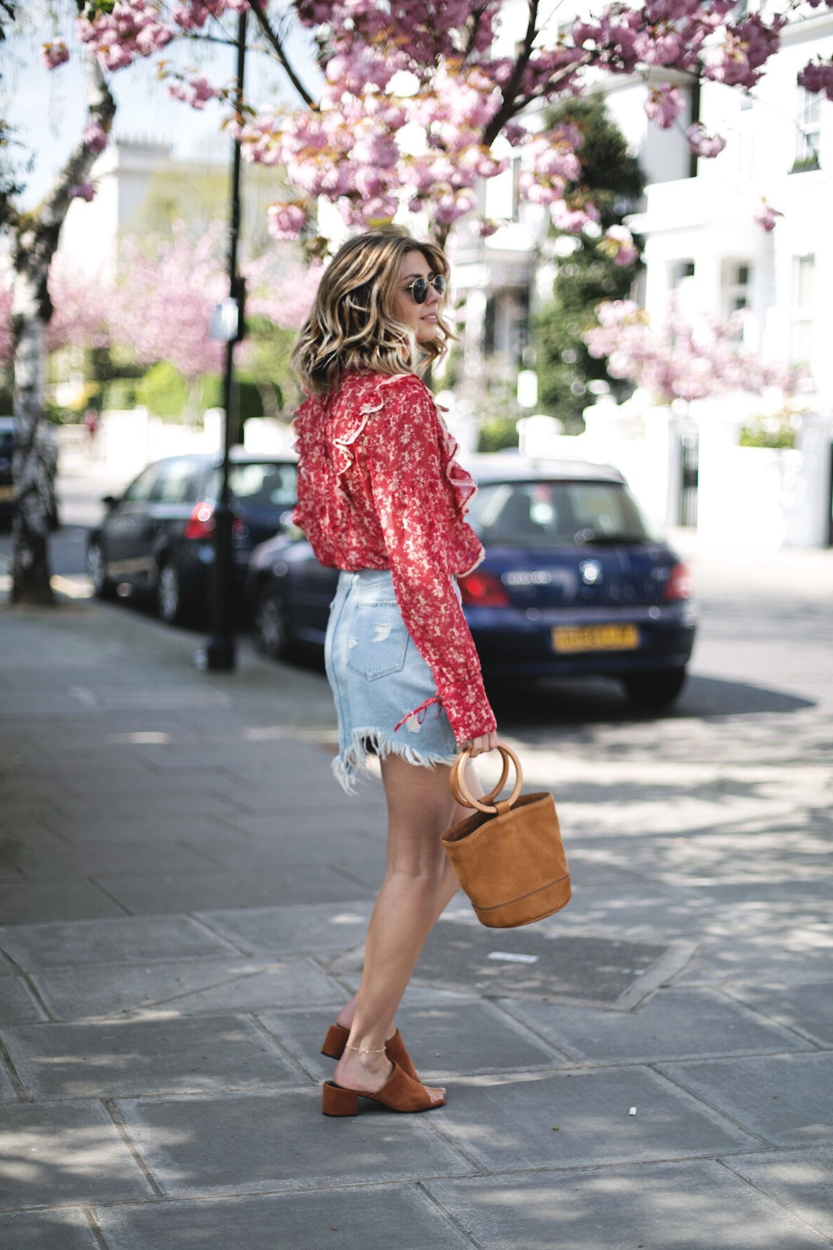 Emma Hill wears red boho blouse, frayed hem denim mini skirt, tan nub Simon Miller Bonsai bag, tan suede sense mules, Ray Ban round metal sunglasses, cute summer outfit