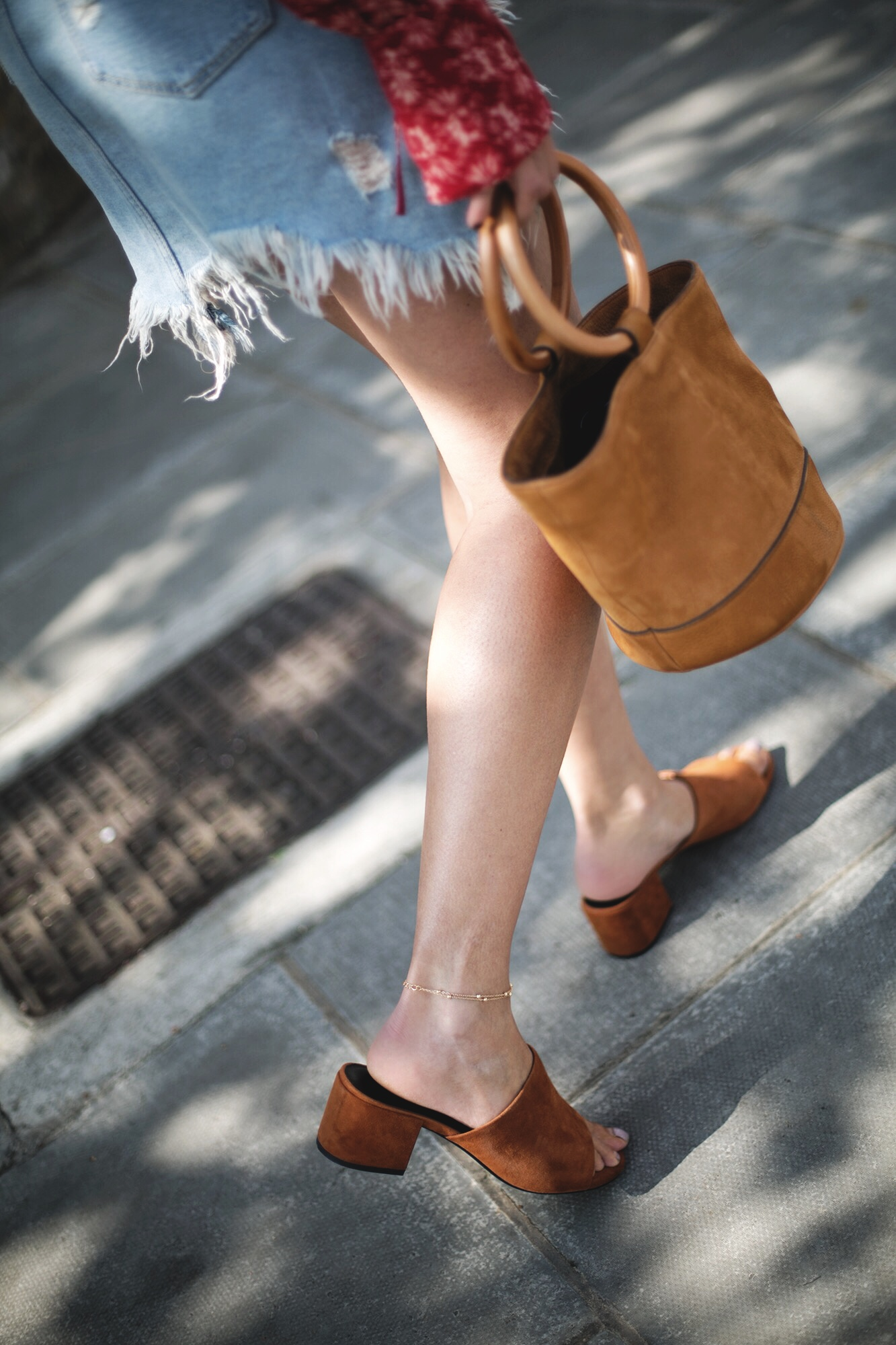 denim mini skirt with frayed hem, tan suede Simon miller bonsai bucket bag, tan suede Senso mules, gold anklet