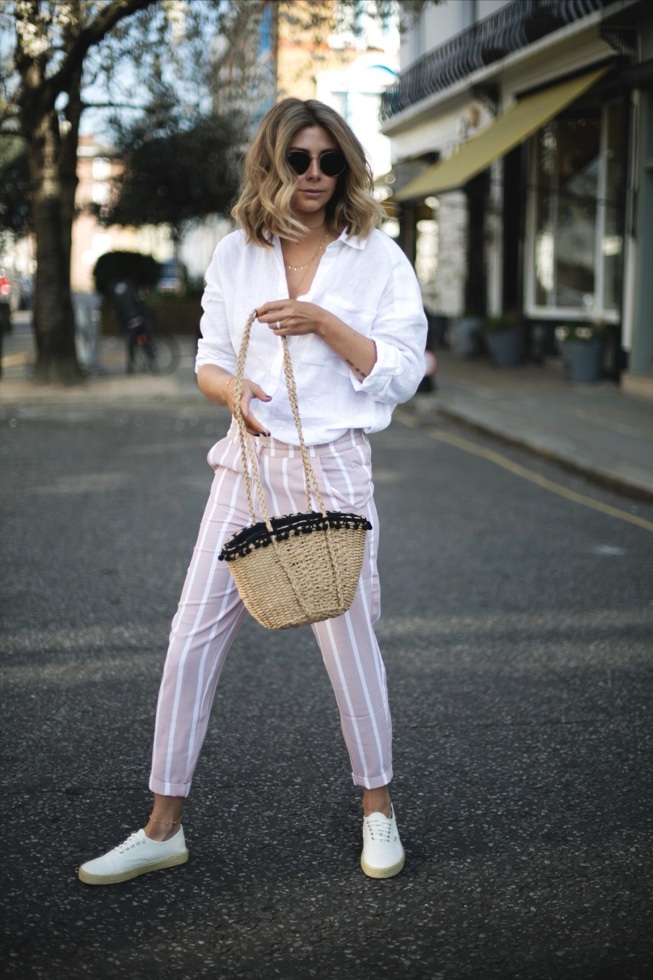 Emma Hill wears pink stripe trousers, white linen shirt, woven basket bag, Vans espadrille lace ups, Ray Ban round metal sunglasses, casual spring summer outfit