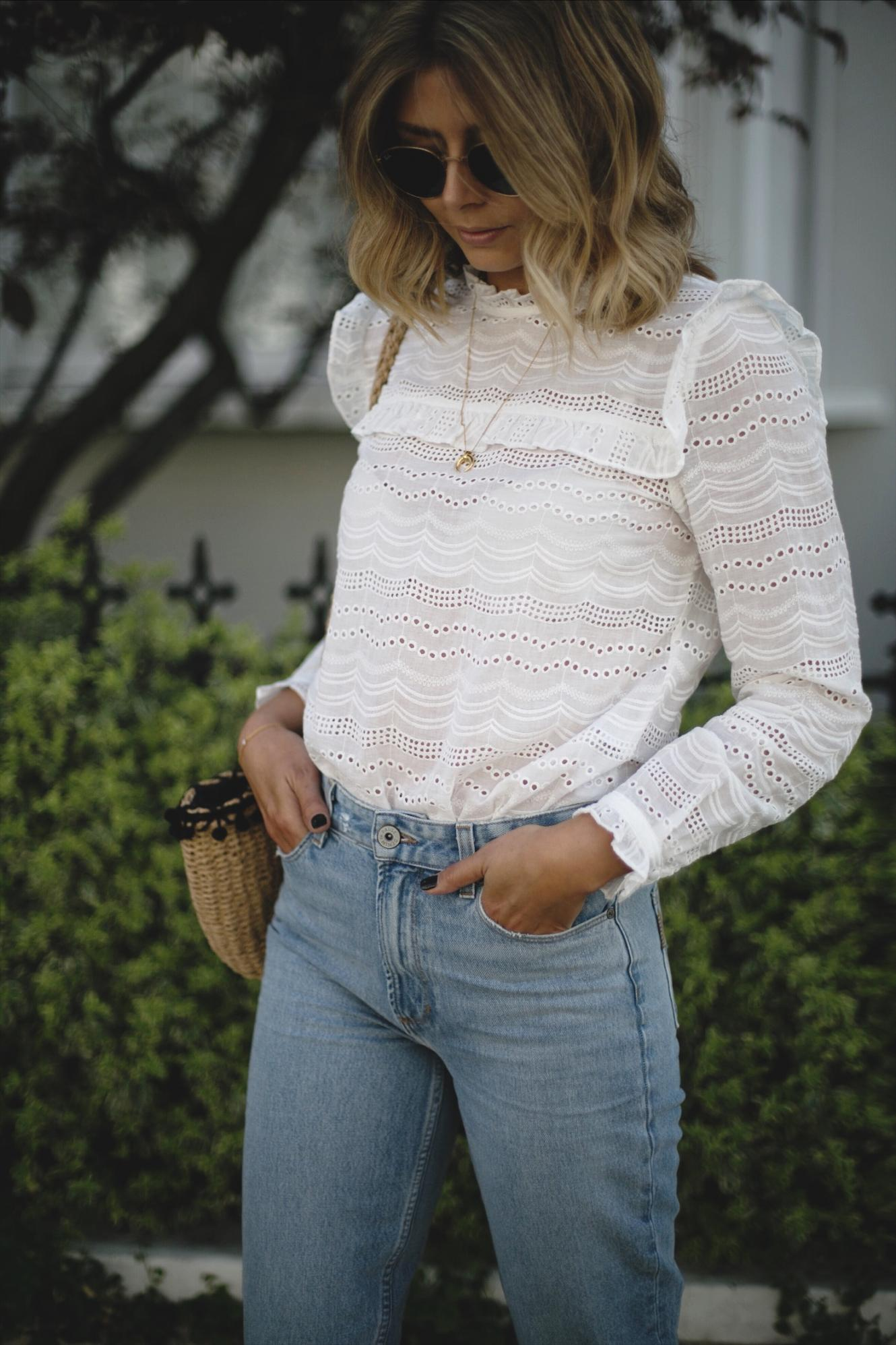 Emma Hill wears cream broderie anglais blouse, bleach wash high waisted jeans, straw basket bag with pom poms
