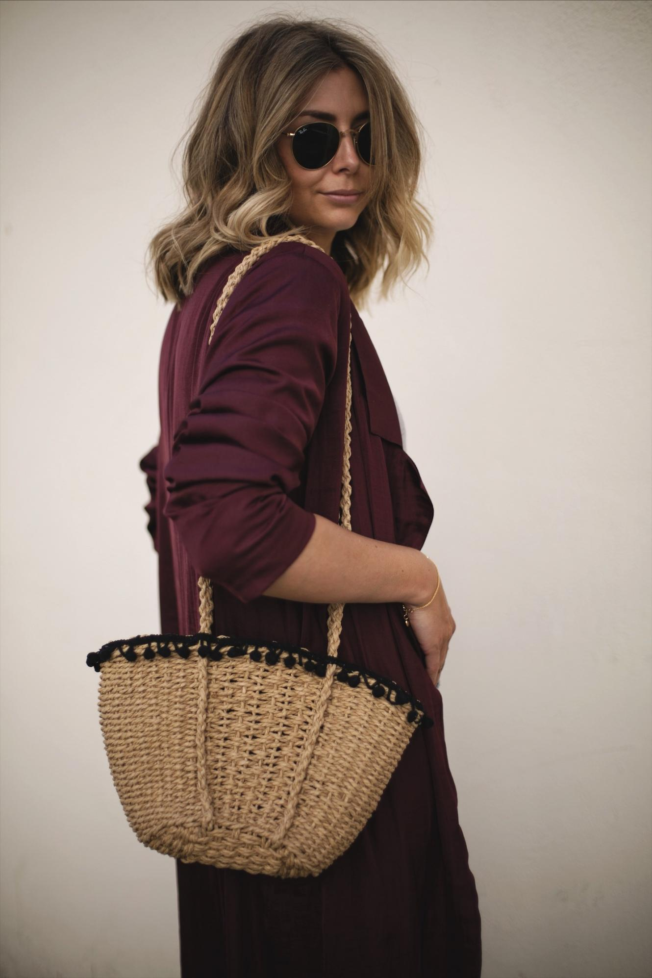 Emma Hill wears wine coloured long silky duster jacket kimono, straw basket bag with pom pom detail, gold Ray-Ban round metal sunglasses, blonde lob hair