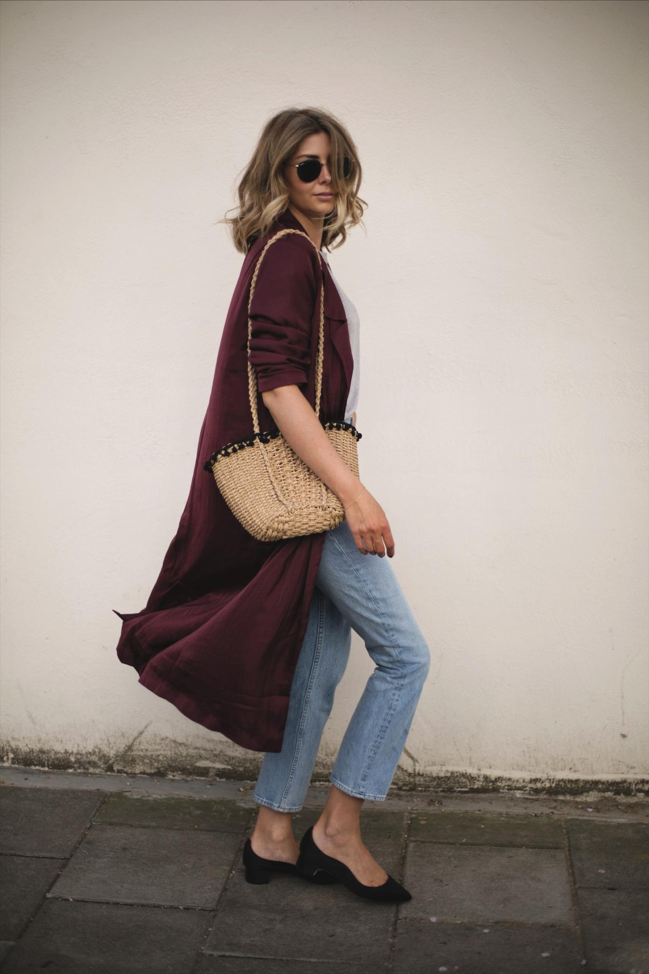 Emma Hill wears deep purple wine silky duster jacket kimono, straw basket bag with pom pom detail, grey t-shirt, cropped straight leg jeans, Dune x Rupert Sanderson low block heels, outfit ideas for Spring