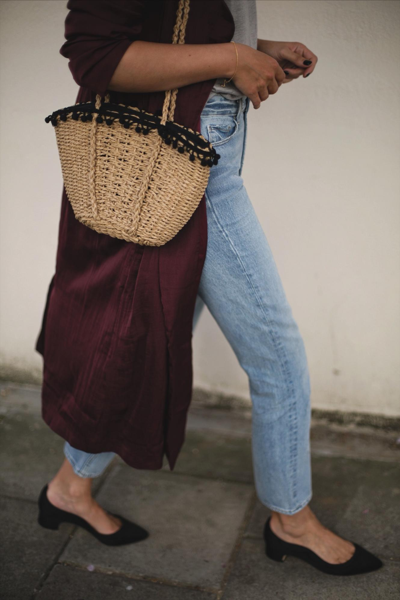 straw basket bag with pom pom detail, light wash straight leg jeans, long deep purple silky duster jacket kimono, black satin Dune x Rupert Sanderson low block heels