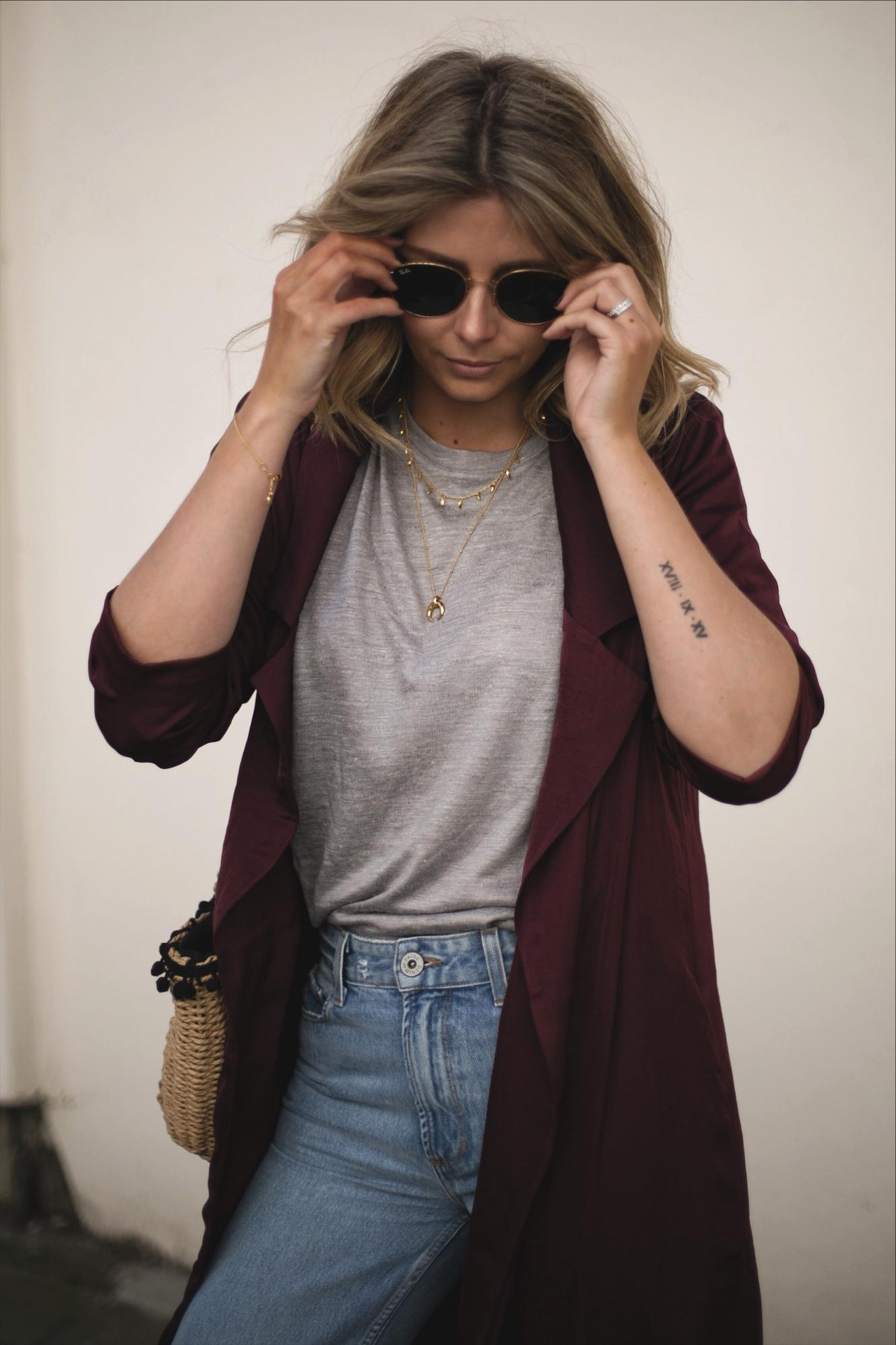 Emma Hill wears wine silky duster jacket, grey basic linen t-shirt, gold jewellery, straw basket bag, light wash Paige jeans, Ray Ban round metal gold sunglasses, tiny Roman numerals arm tattoo