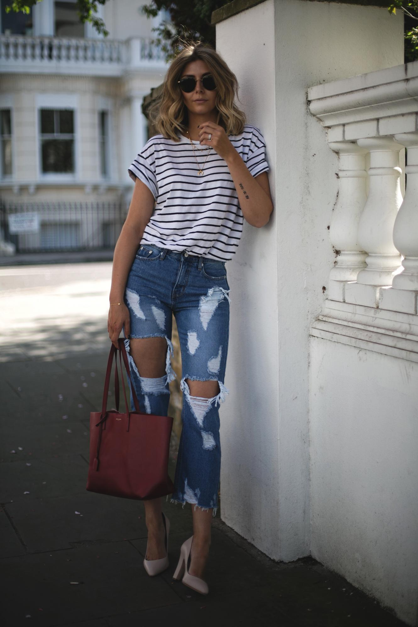 Emma Hill of EJSTYLE wears stripe t-shirt, ripped destroyed jeans, red Saint Laurent YSL shopper tote bag, nude heels, gold layered necklaces, Spring outfit