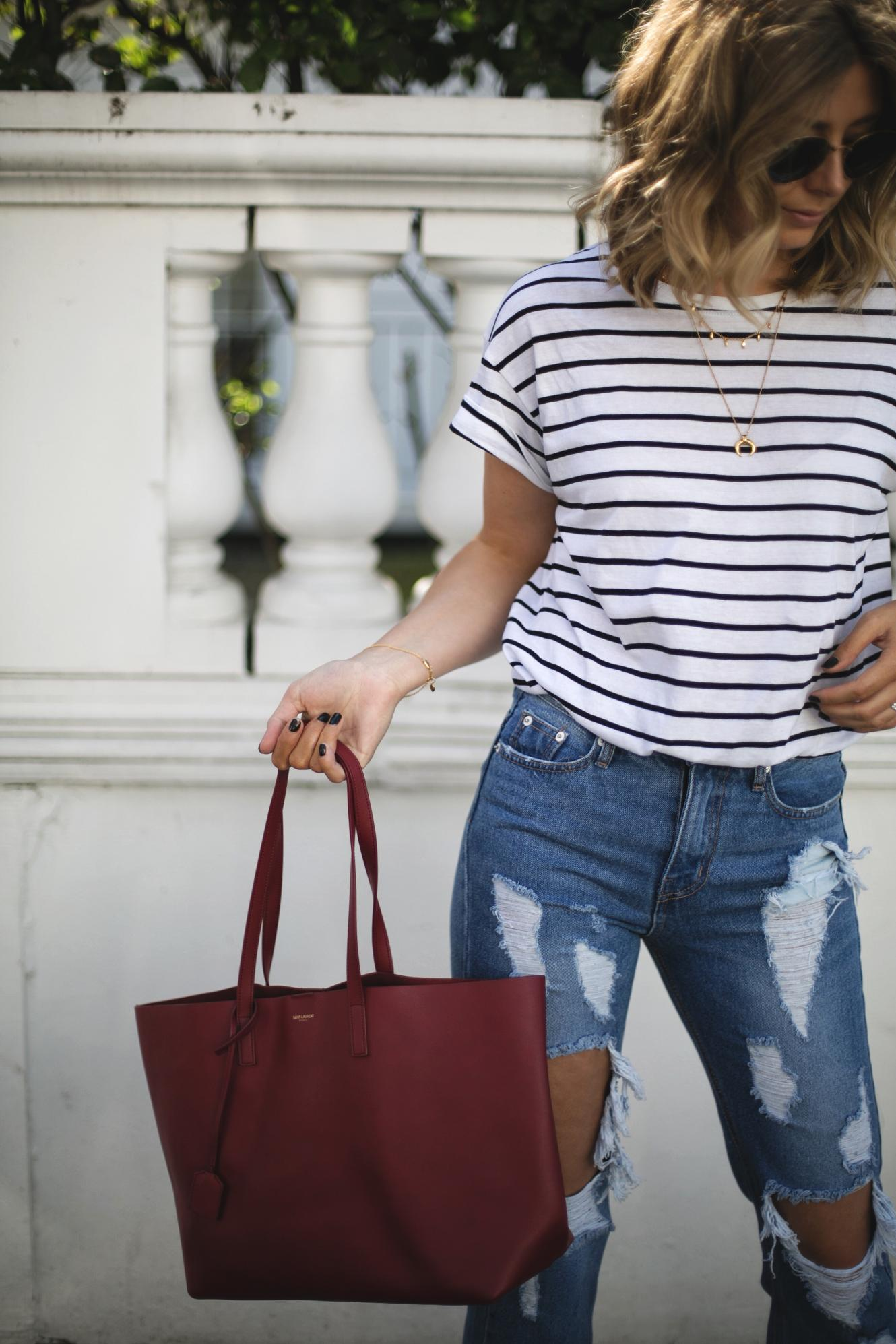 Emma Hill of EJSTYLE wears stripe t-shirt, ripped destroyed jeans, red Saint Laurent YSL shopper tote bag, gold layered necklaces, Spring outfit