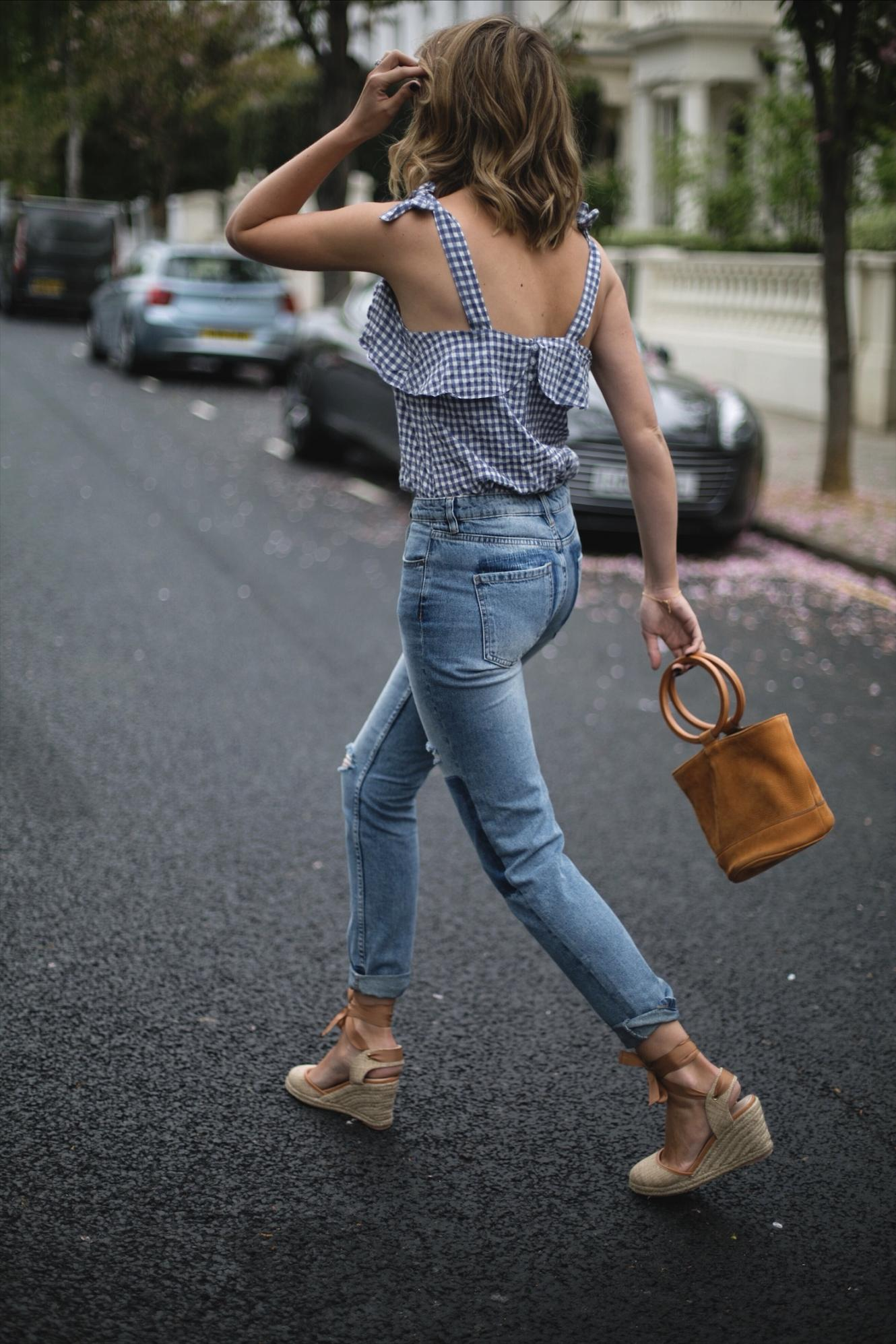 Emma Hill wears gingham top, rolled up hem jeans, wedge espadrilles, tan suede Simon Miller ring handle bag