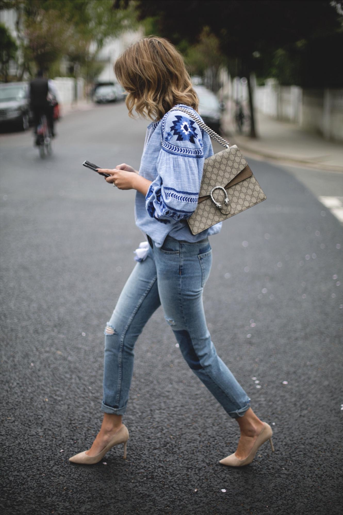 Emma Hill wears embroidered blue top with balloon sleeves, cuffed mid wash jeans, street style photography tips