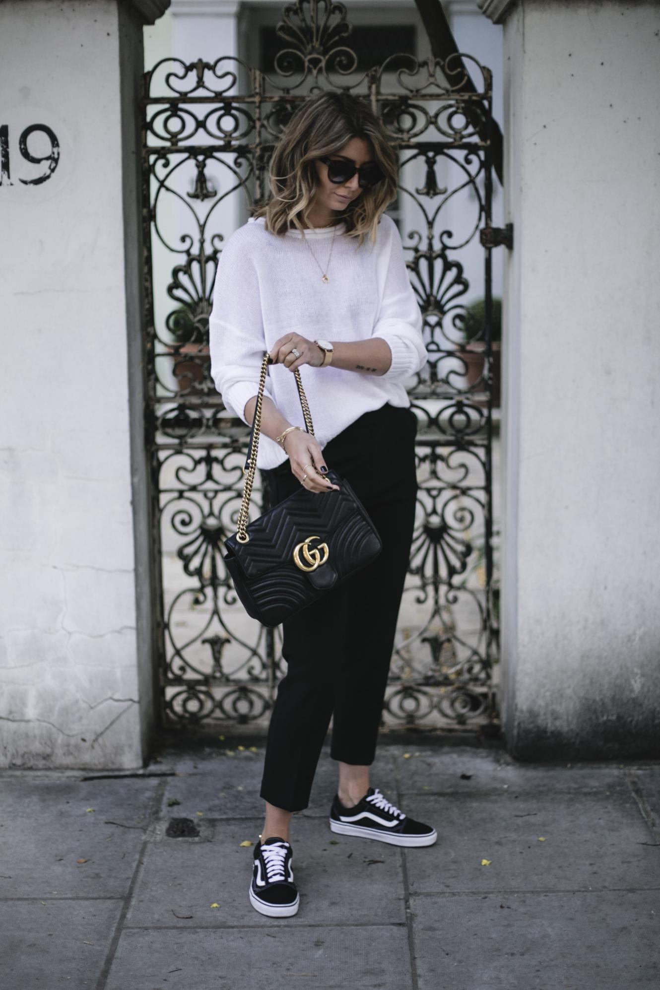 Emma Hill wears Vans old skull, white summer knit, black tailored trousers, Gucci Marmont bag, casual Spring outfit