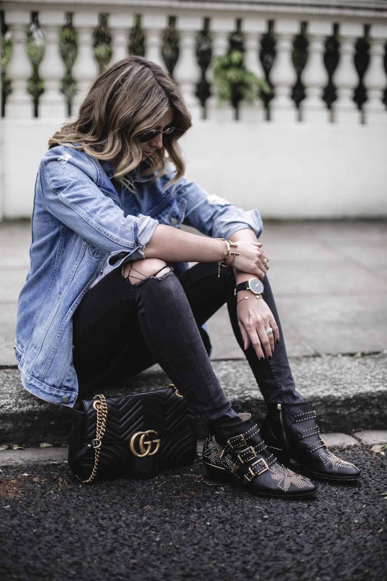 Emma Hill wears oversized denim jacket, black skinny ripped knee jeans, Gucci Marmont bag, Chloe Susanna ankle boots with gold studs, Spring Summer casual outfit