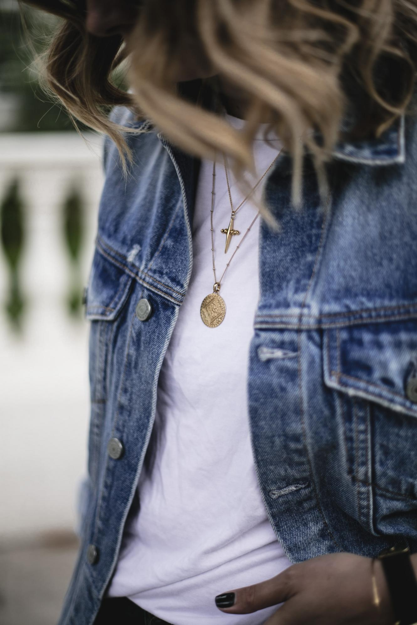 Emma Hill wears denim jacket, white t-shirt, gold layered necklaces