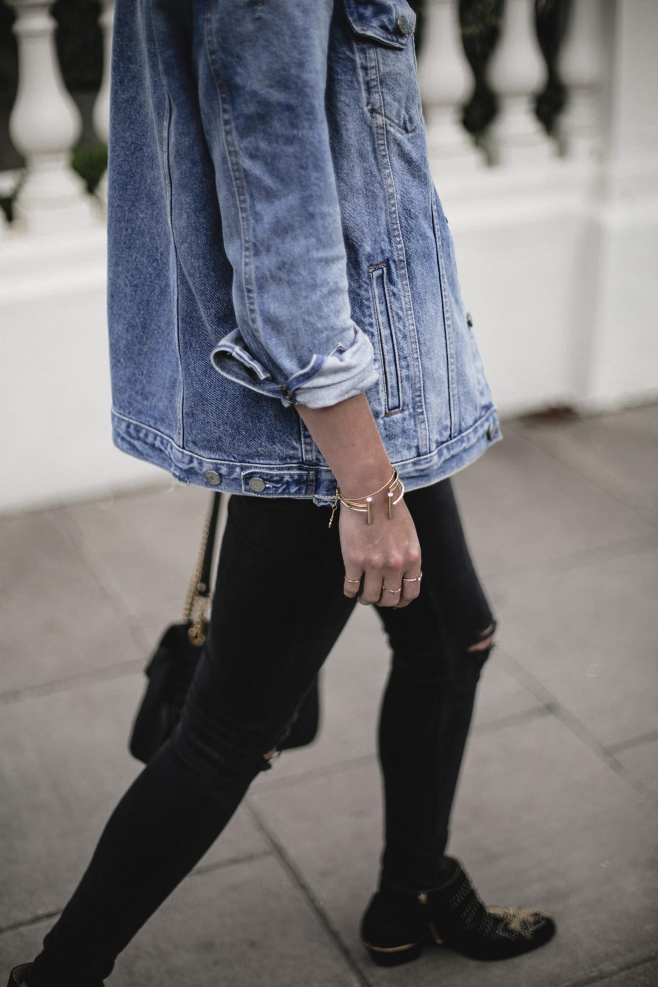Emma Hill wears oversized denim jacket, gold bracelets, Chloe Susanna ankle boots, black skinny jeans with knee rips