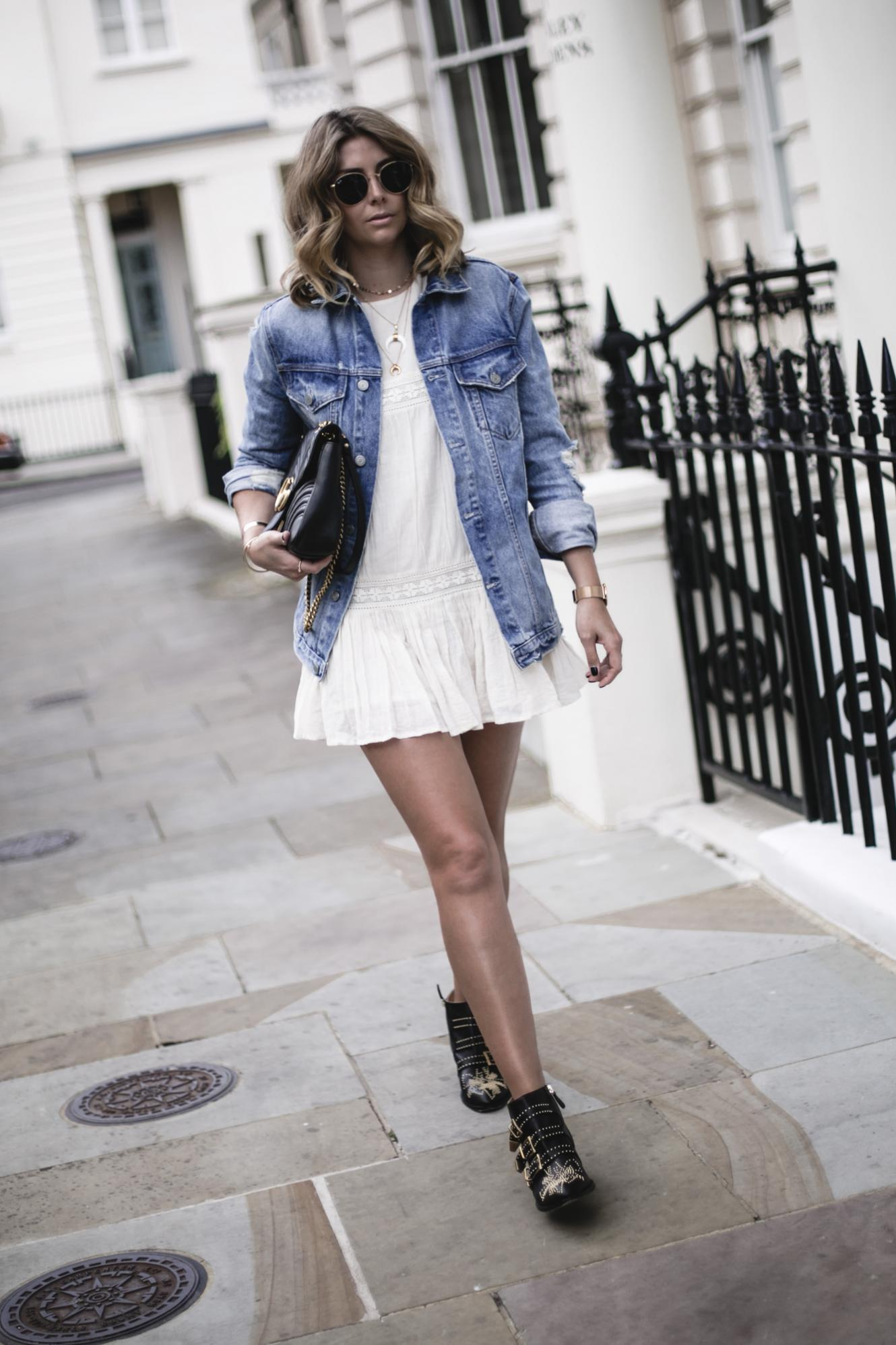 Emma Hill wears oversized denim jacket, boho mini dress, Gucci Marmont bag, layered gold horn necklaces, Chloe Susanna boots, summer outfit