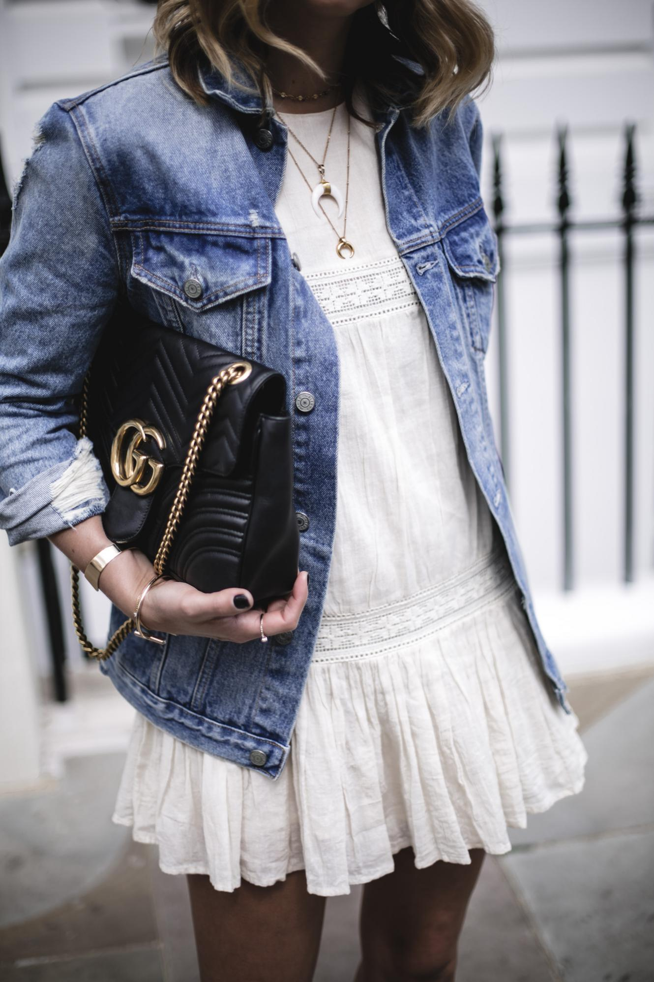 Emma Hill wears oversized denim jacket, boho mini dress, Gucci Marmont bag, layered gold horn necklaces, summer outfit