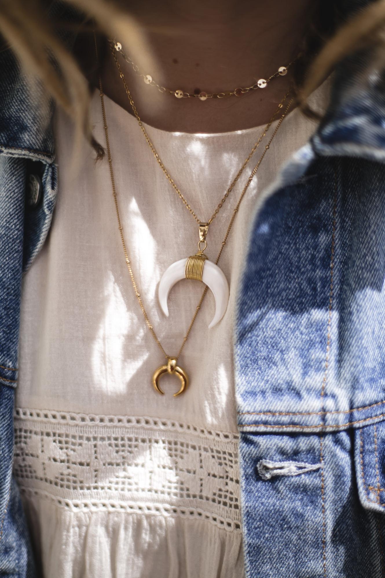 Emma Hill wearing denim jacket, boho dress, layered gold horn necklaces