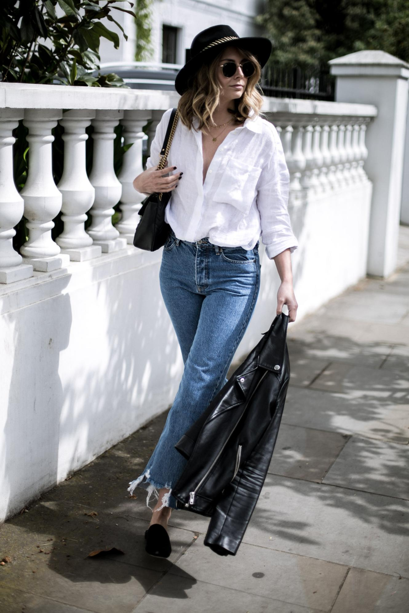 Emma Hill of EJSTYLE wears white linen shirt, distressed hem jeans, black leather biker jacket, fedora with gold band, Gucci Marmont bag, satin mules, casual spring outfit