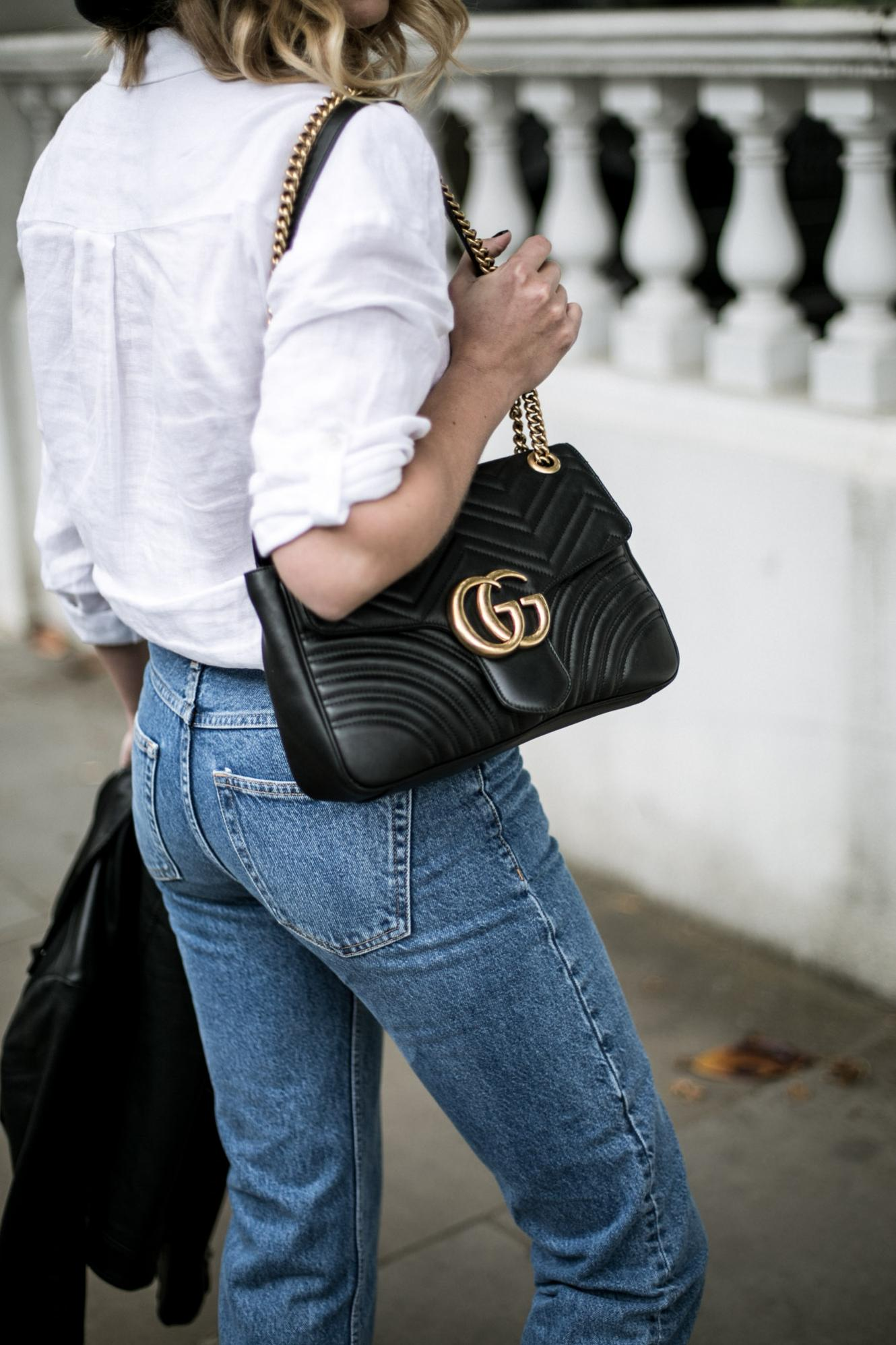 gucci black leather marmot bag, white linen shirt, jeans, biker jacket