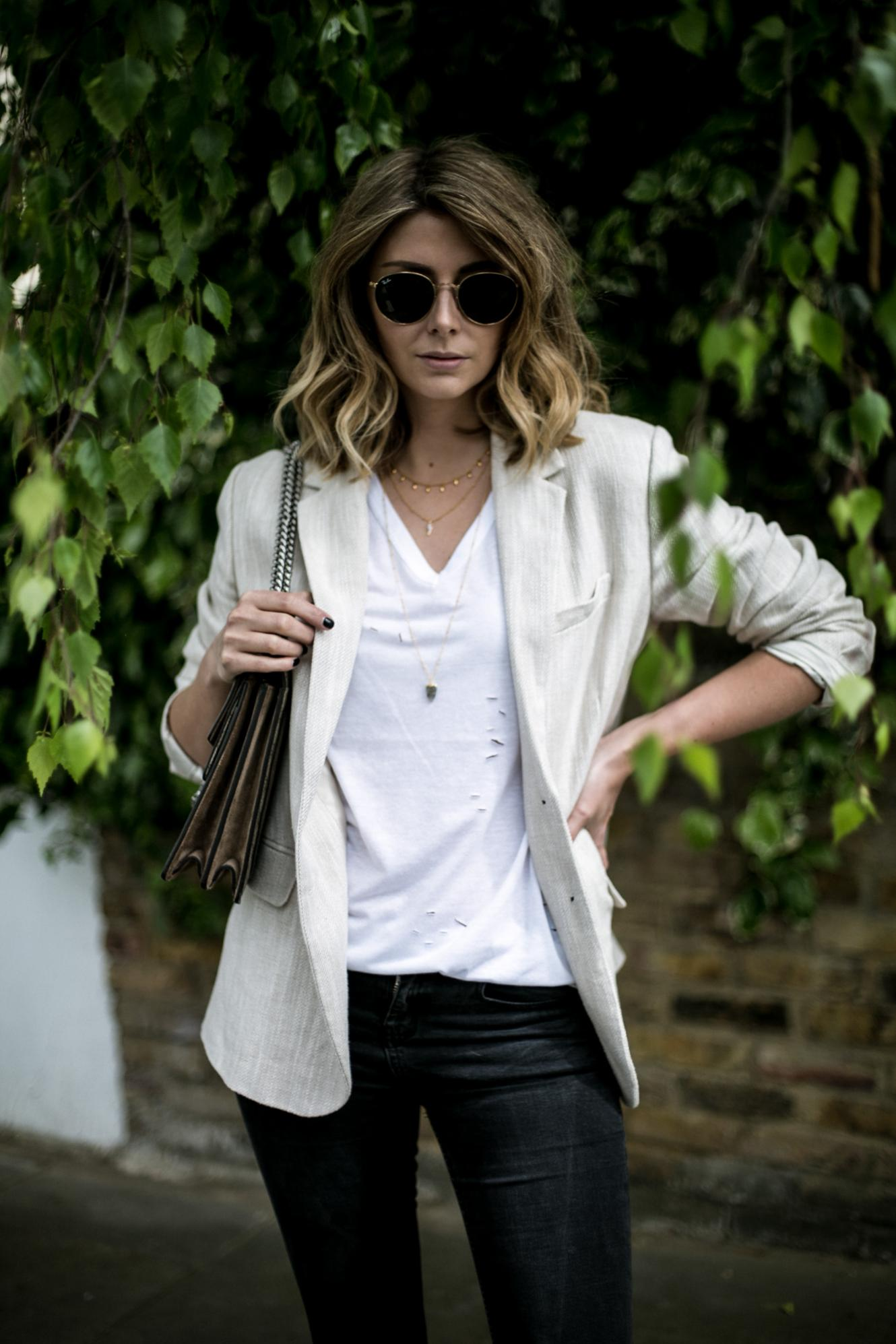 Emma Hill from EJSTYLE wears gold layered necklaces, white nibbled t-shirt, beige linen blazer, gold round Ray-Ban sunglasses
