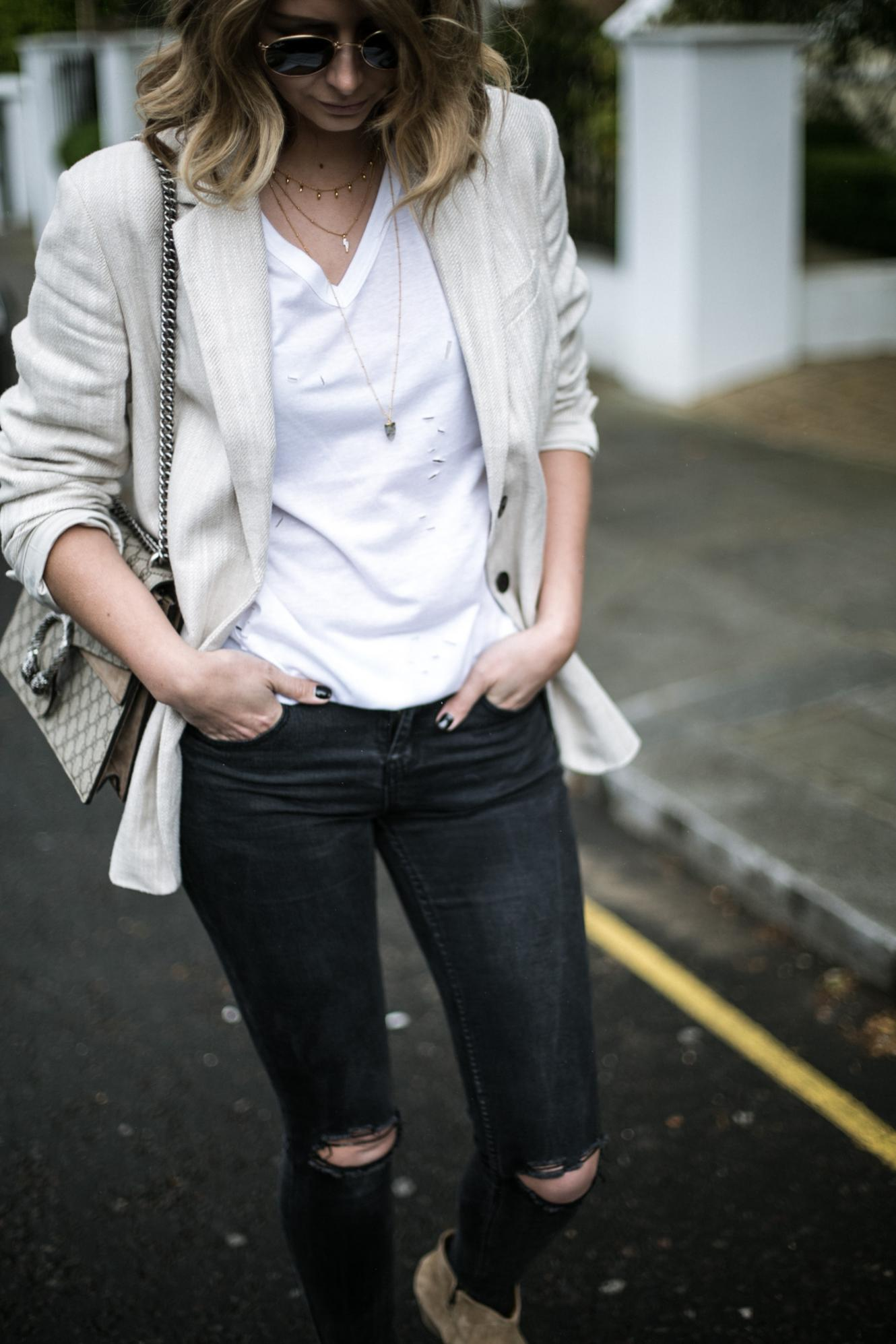 Emma Hill from EJSTYLE wears gold layered necklaces, white nibbled t-shirt, beige linen blazer, gold round Ray-Ban sunglasses, black skinny jeans with ripped knees