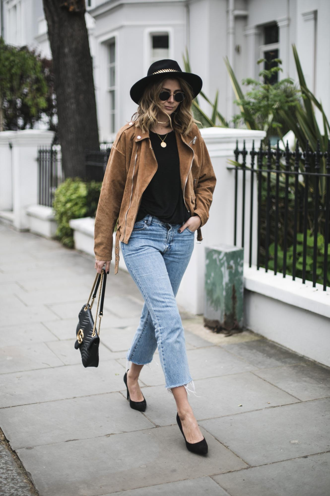 Emma Hill from EJSTYLE wears tan suede biker jacket, black t-shirt, cropped flare raw hem jeans black Gucci Marmont bag, Black suede heeled pumps, black fedora, spring outfit