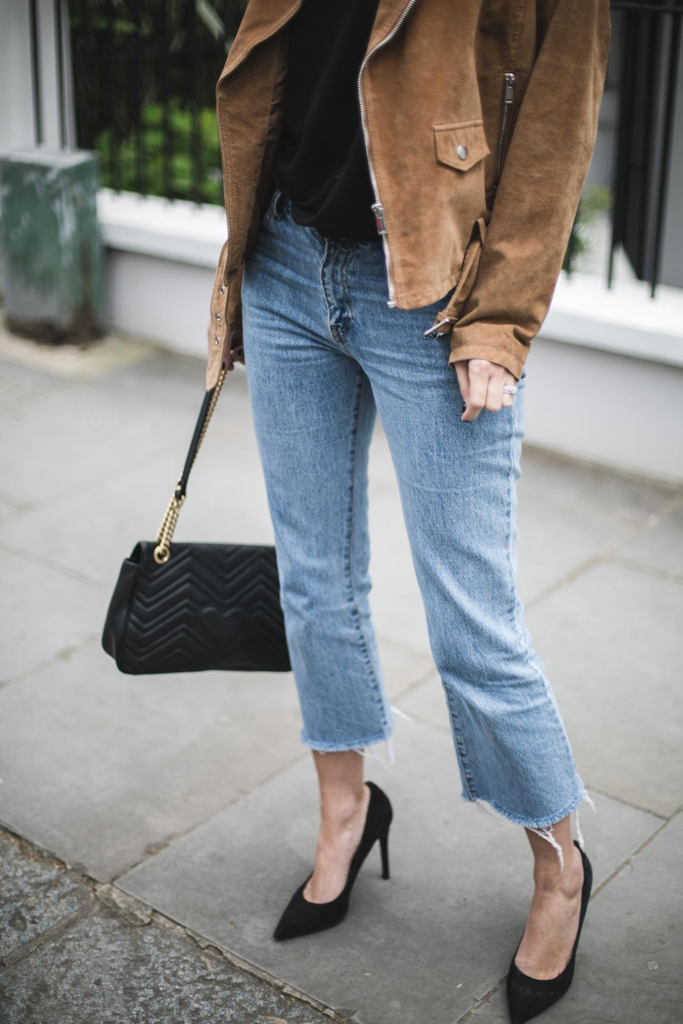 Emma Hill from EJSTYLE wears tan suede biker jacket, black t-shirt, cropped flare raw hem jeans black Gucci Marmont bag, Black suede heeled pumps,