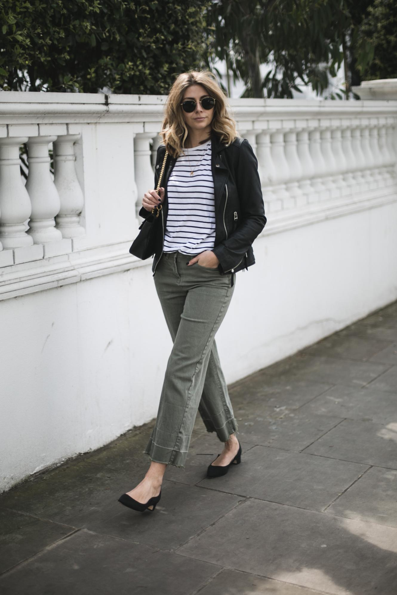 Emma Hill of EJSTYLE wears black leather biker jacket, stripe t-shirt, wide leg khaki trousers, Gucci Marmont bag, low block heel pumps, Spring outfit