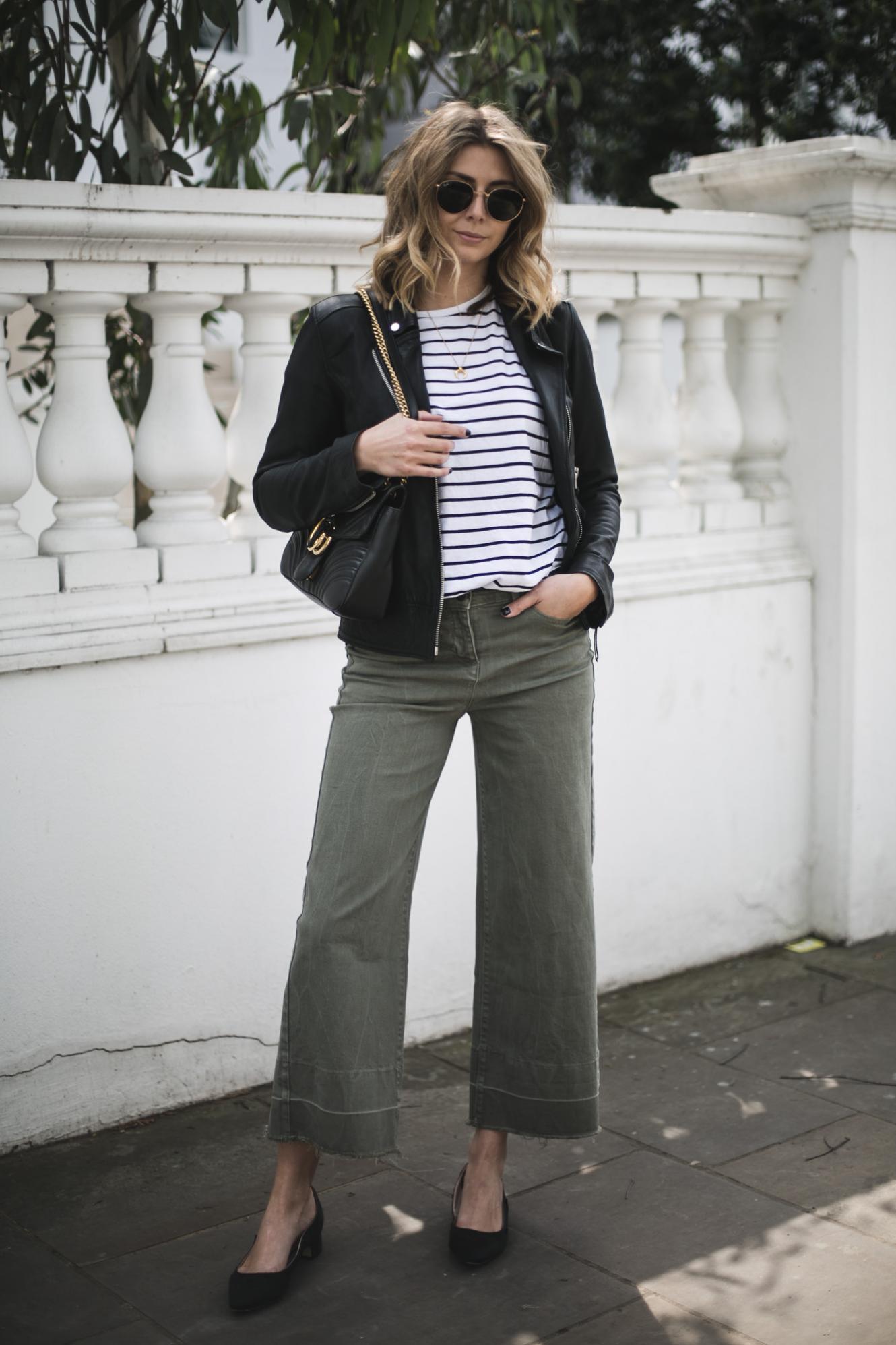 Emma Hill of EJSTYLE wears black leather biker jacket, stripe t-shirt, wide leg khaki trousers, Gucci Marmont bag, low block heel pumps, Spring outfit