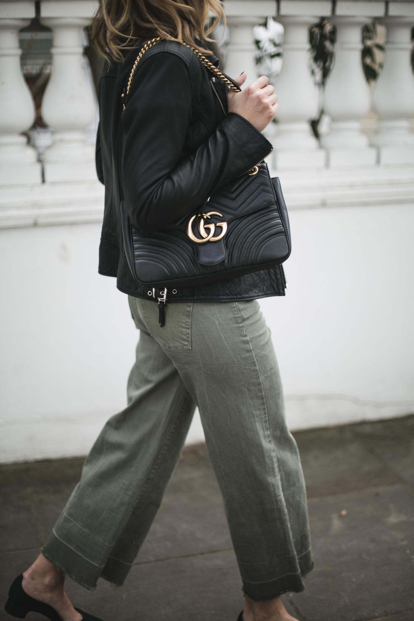 black biker jacket, Gucci medium black leather Marmont bag, wide leg khaki jeans trousers
