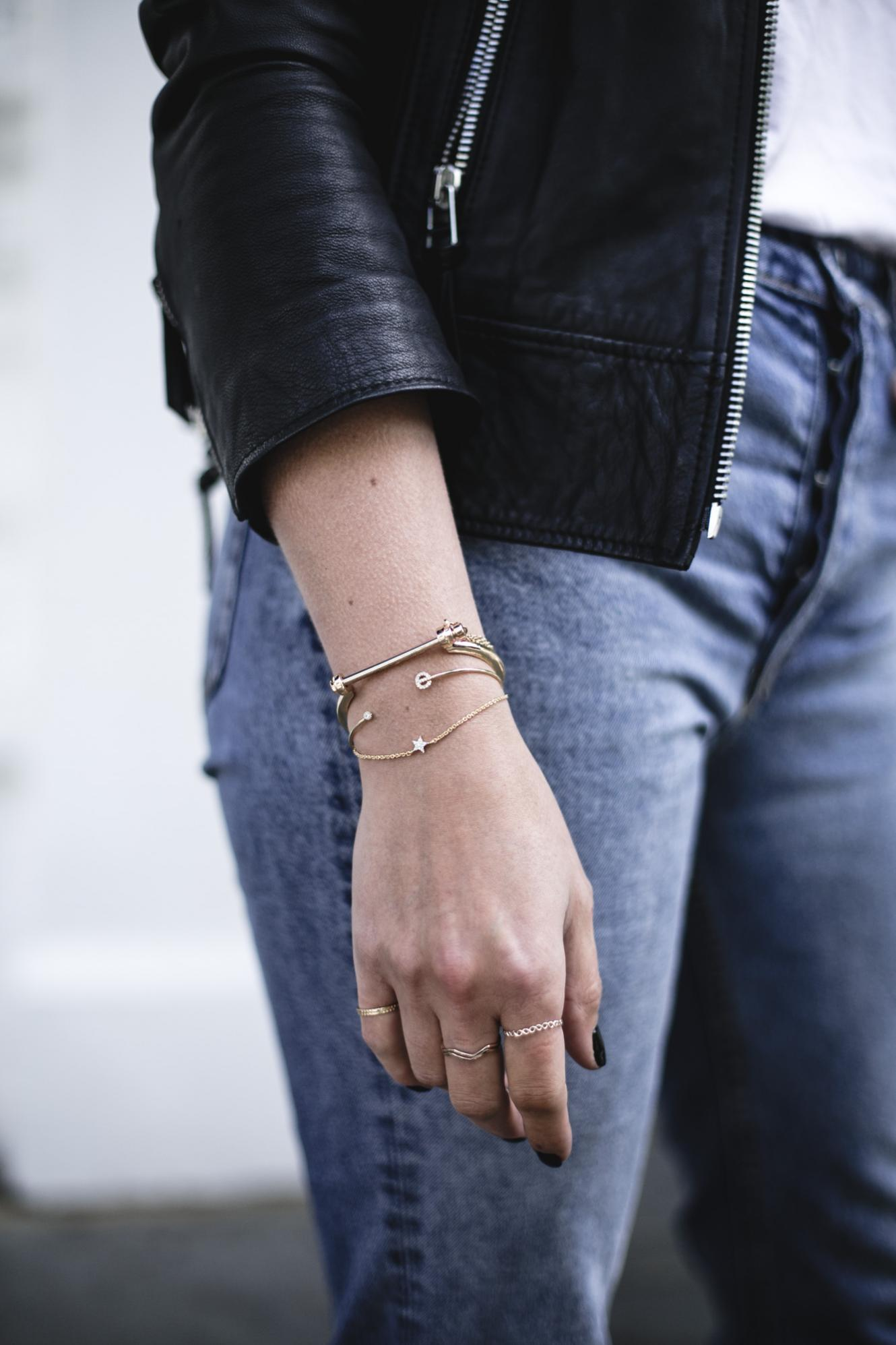 Emma Hill wears gold bracelets, black biker jacket and jeans