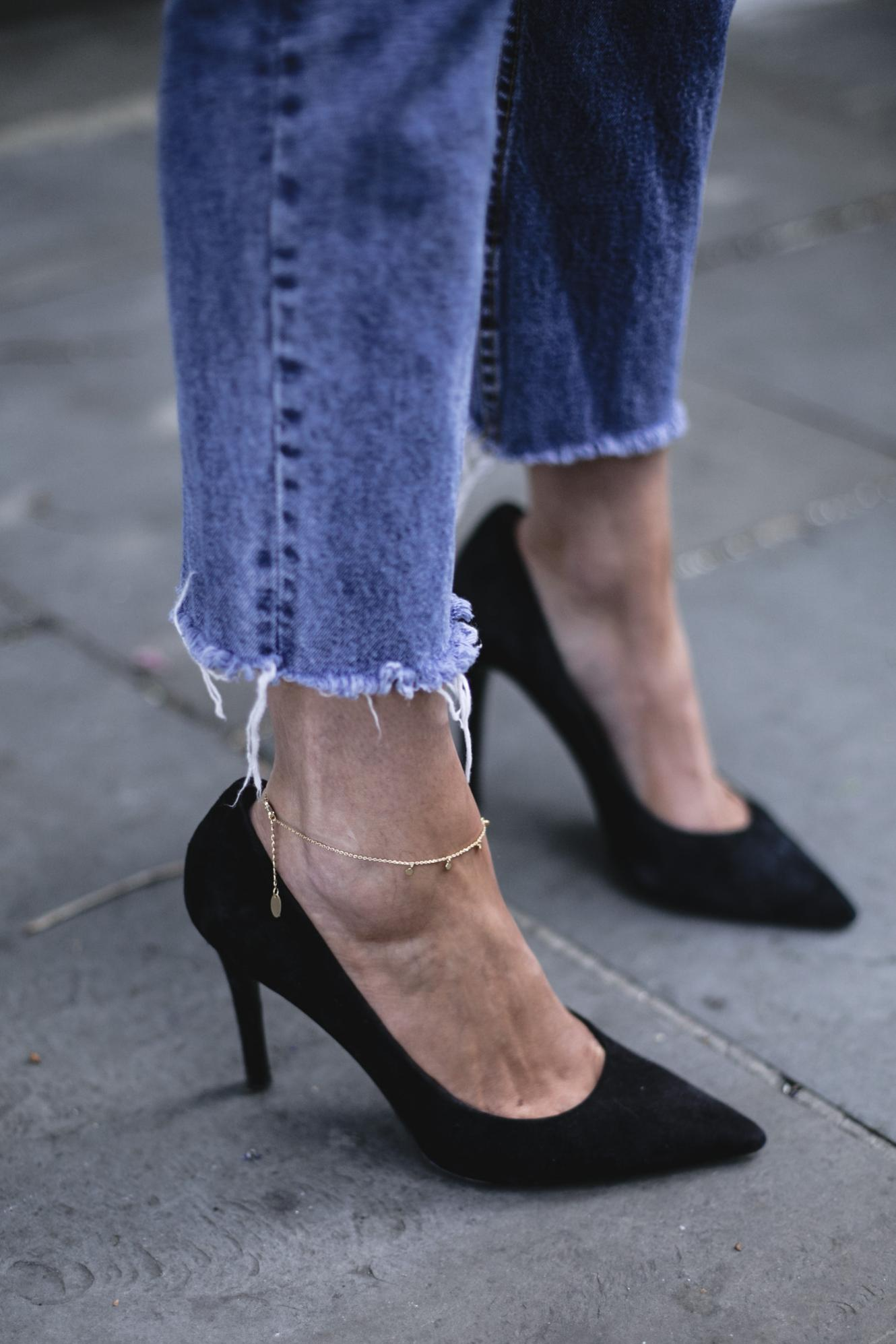 Emma Hill wears frayed raw hem jeans, gold anklet, black suede court shoes