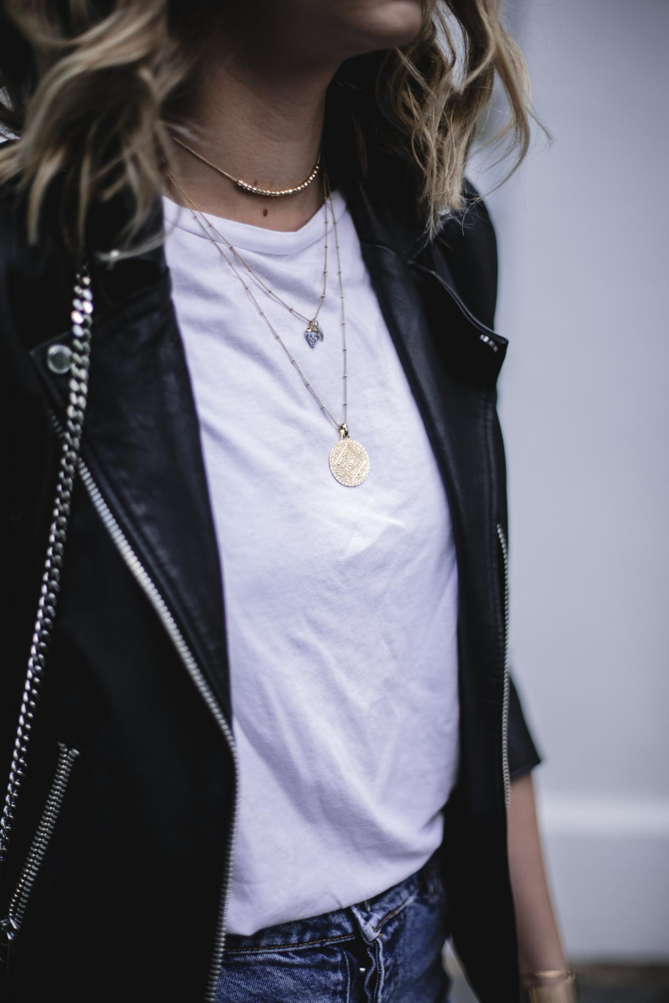 Emma Hill wears gold layered necklace, black biker jacket, basic white t-shirt