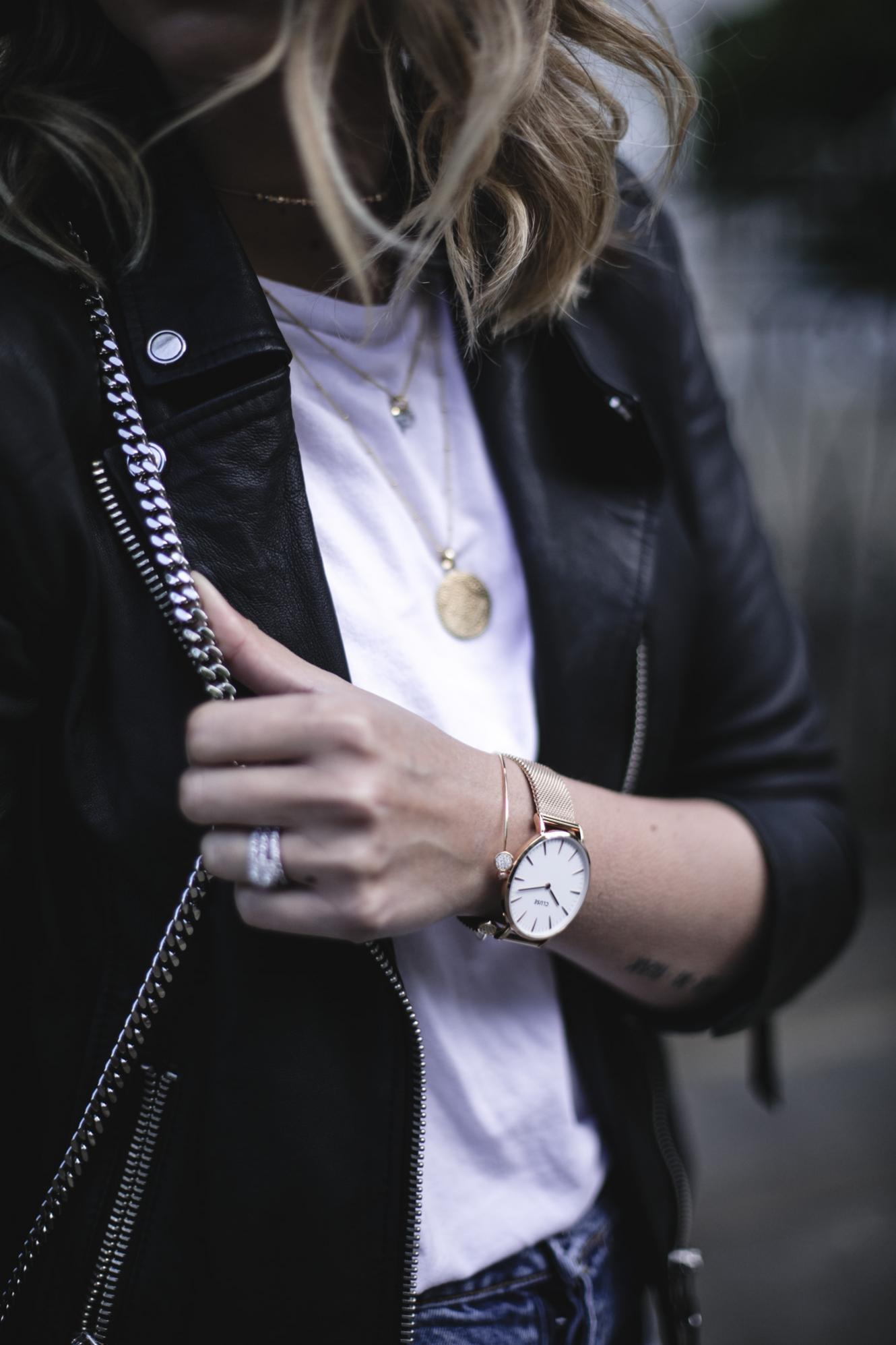 Emma Hill wears layered gold necklaces, white t-shirt, black biker jacket