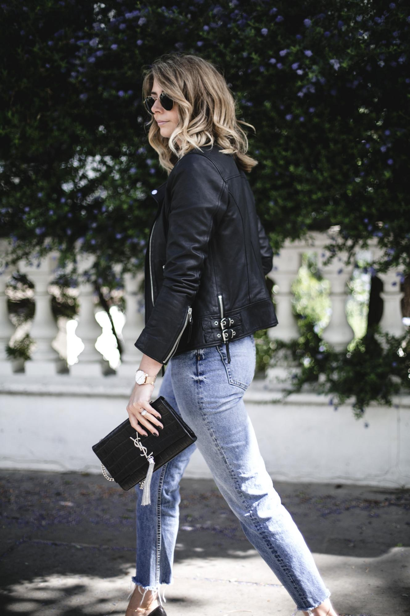 Emma Hill wears black leather biker jacket, frayed hem jeans, YSL tassel bag