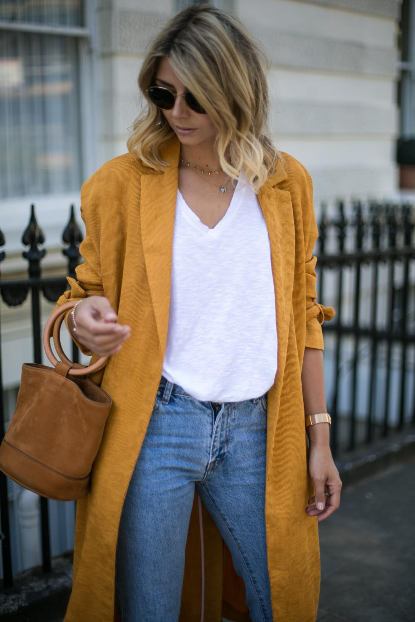 Emma Hill wears Mustard duster coat, cropped frayed jeans, basic white t shirt, Simon Miller Bonsai bag, summer outfit