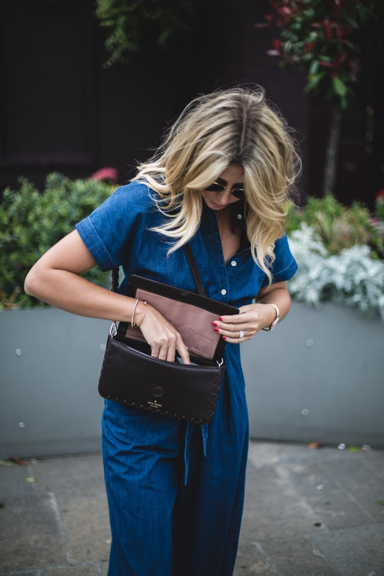 Emma Hill wears Kate Spade Denim jumpsuit, Kate Spade Baja shoulder bag, summer outfit