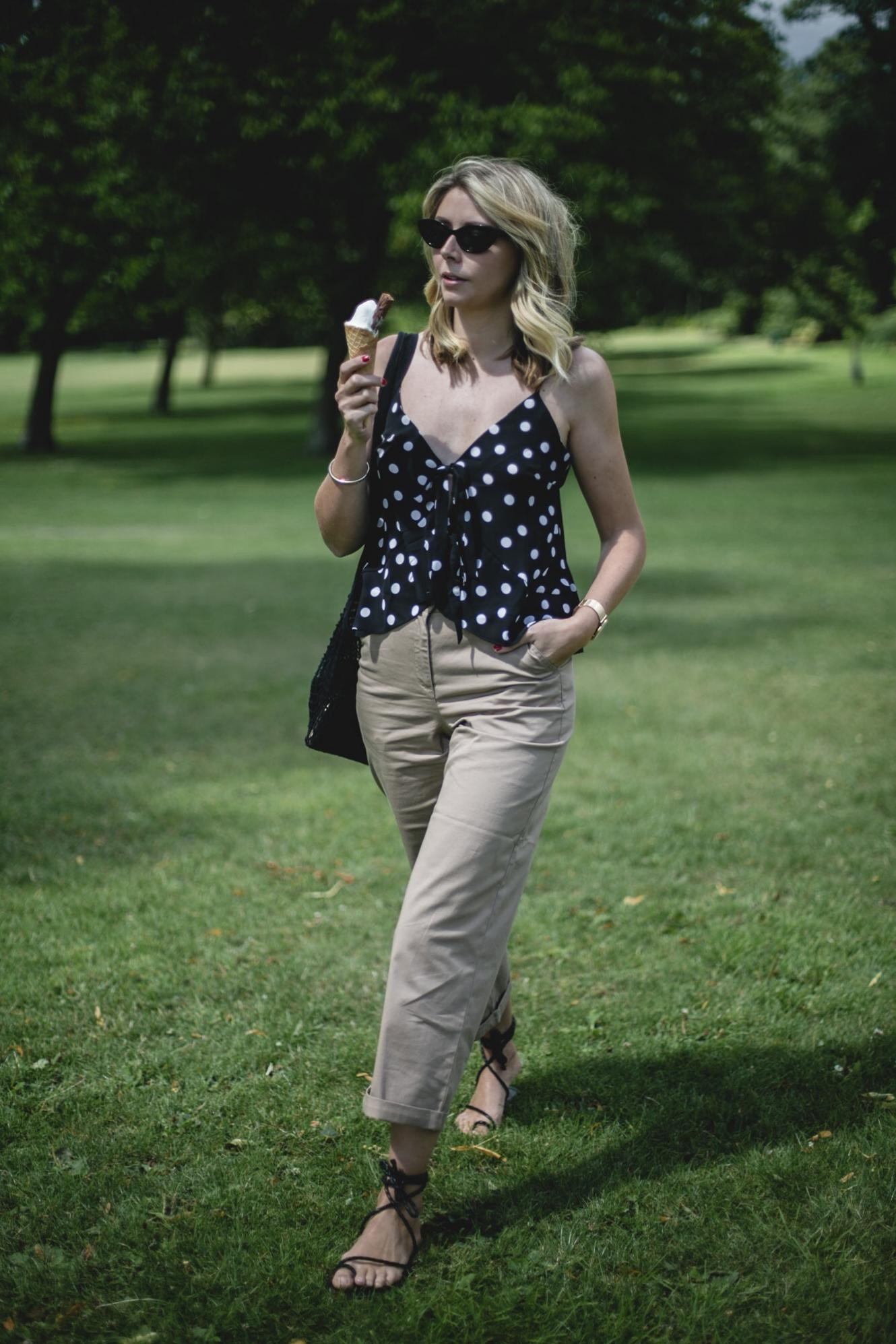 Emma Hill wears polka dot tie front cami, chino trousers, cat eye sunglasses, black ankle tie sandals, summer outfit