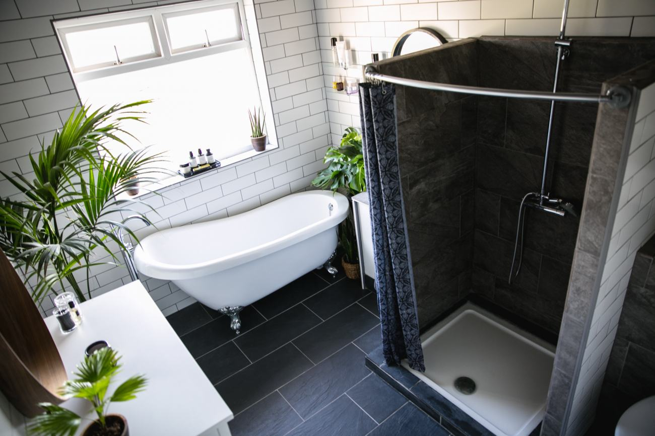 roll top bath, white tiles grey grout, slate floor, bathroom design