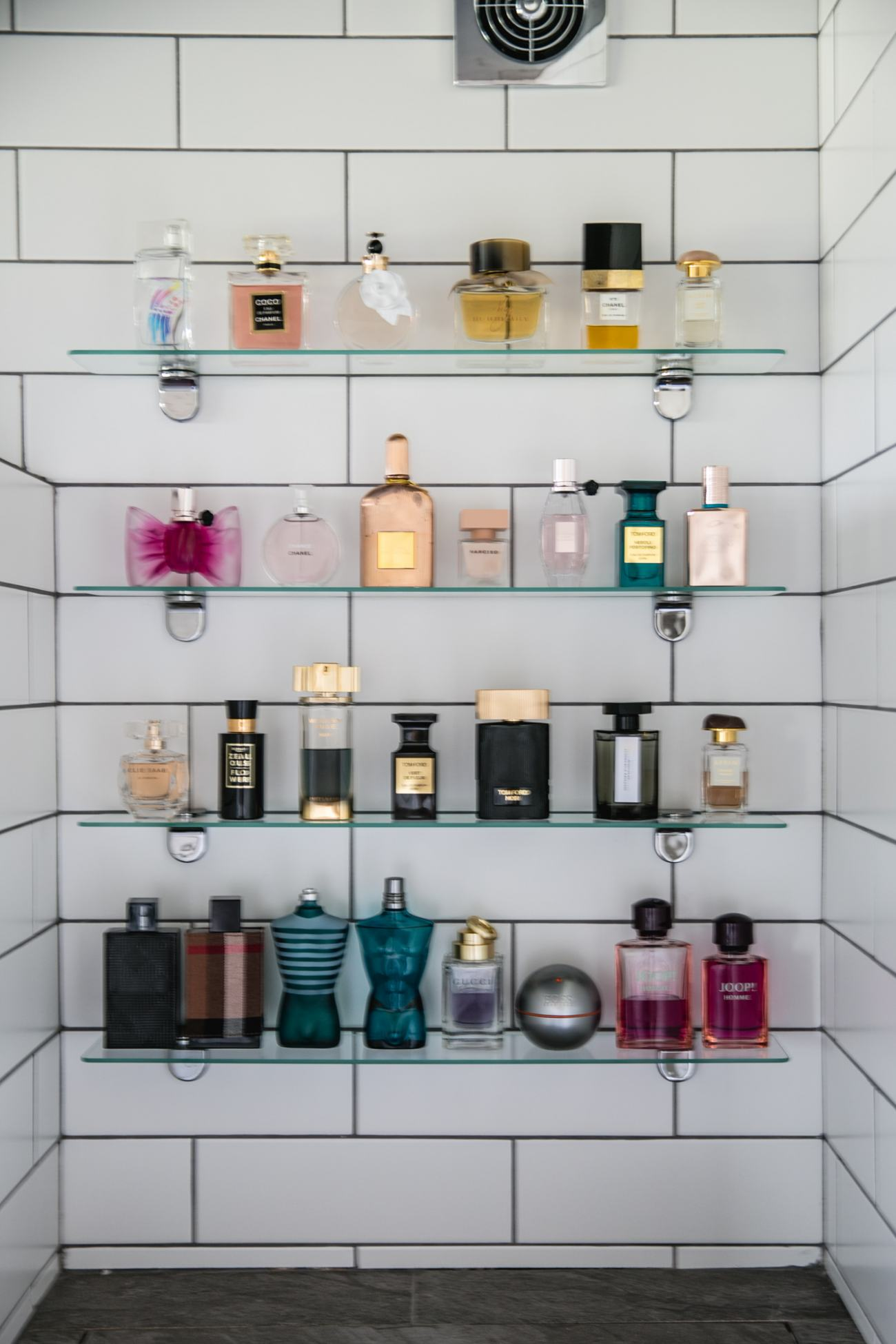 fragrance wall in bathroom, fragrance on display, white subway tiles, grey grout, glass shelves