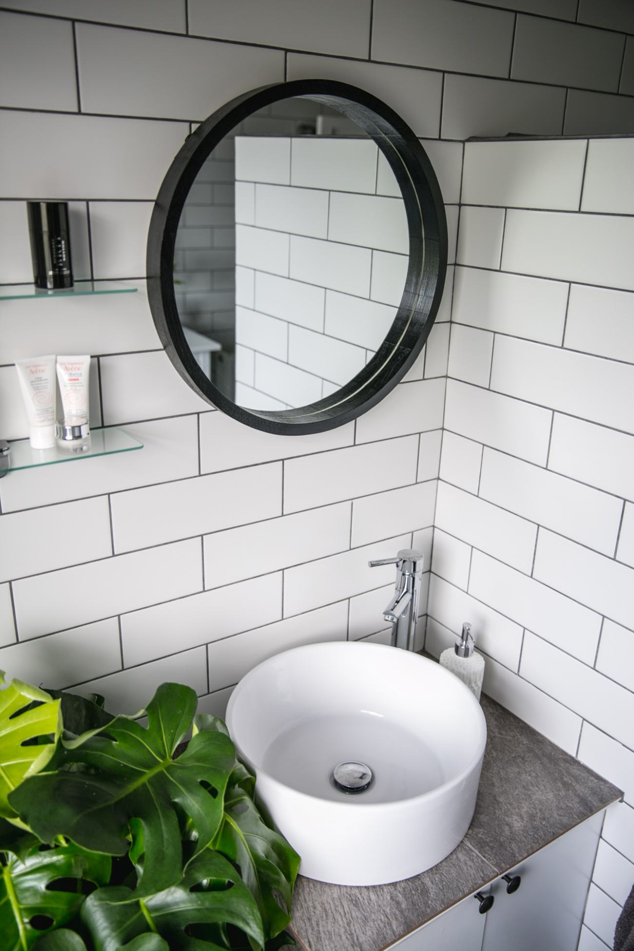 white tiles grey grout, roll top bath, monstera plant, round wall mirror, slate floor, bathroom design